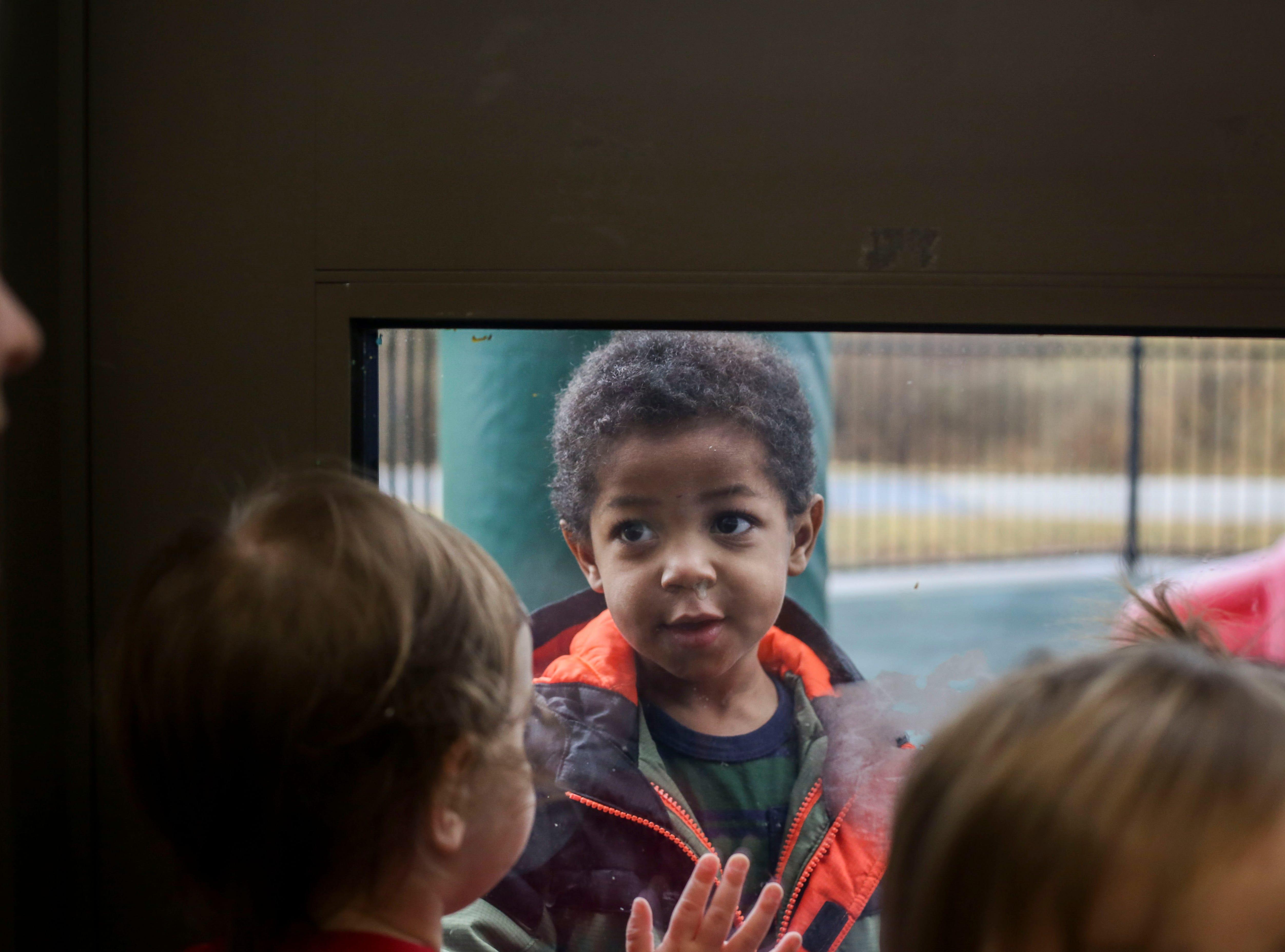 Jayden Nesbitt looks through the glass door into another class during the Early Head Start program at Brooks Elementary School in Brooks, Ky. on Feb. 5, 2019.