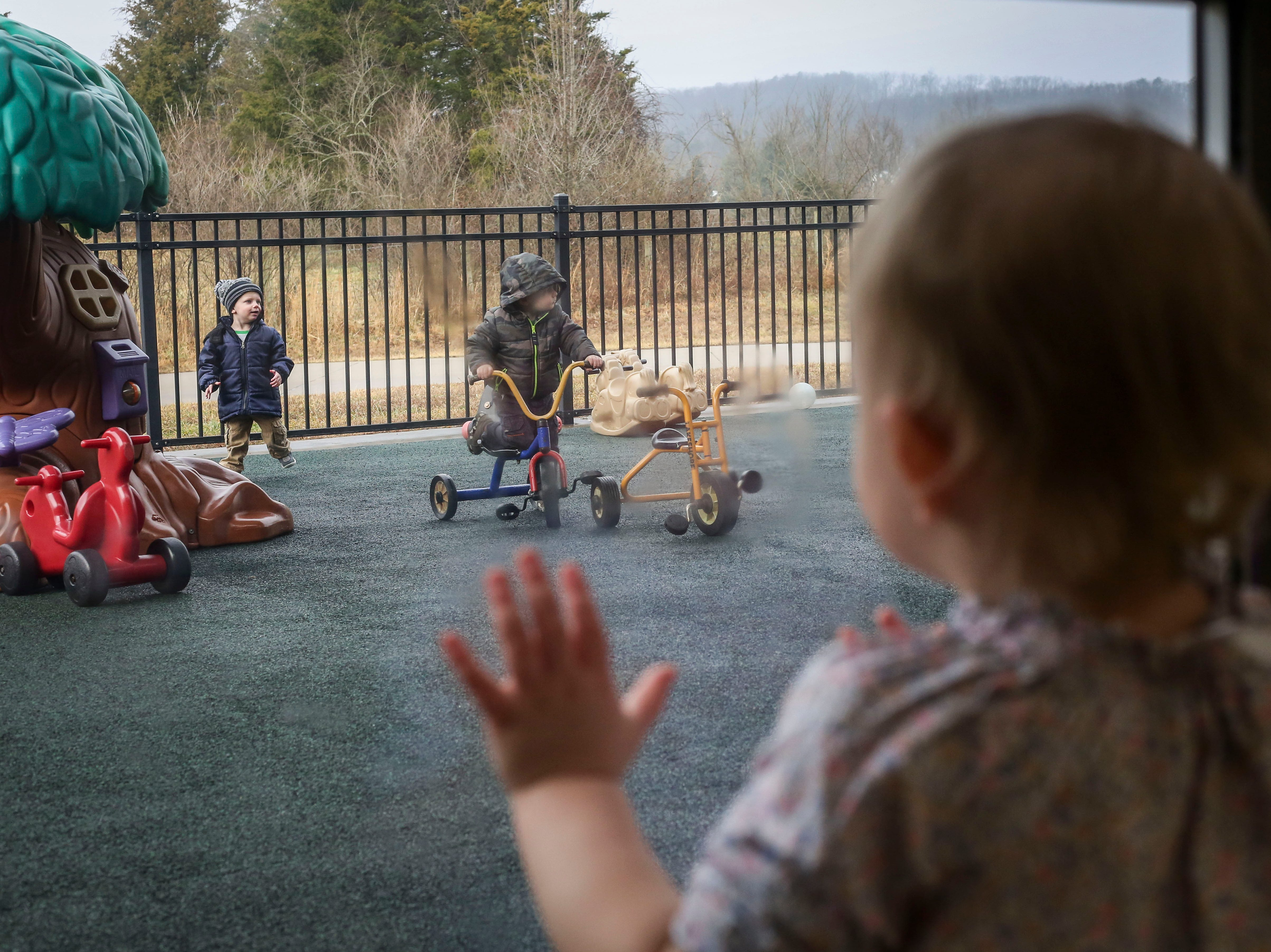 Rose Crutchfield looks through the glass door at another class playing outdoors during the Early Head Start program at Brooks Elementary School in Brooks, Ky. on Feb. 5, 2019.