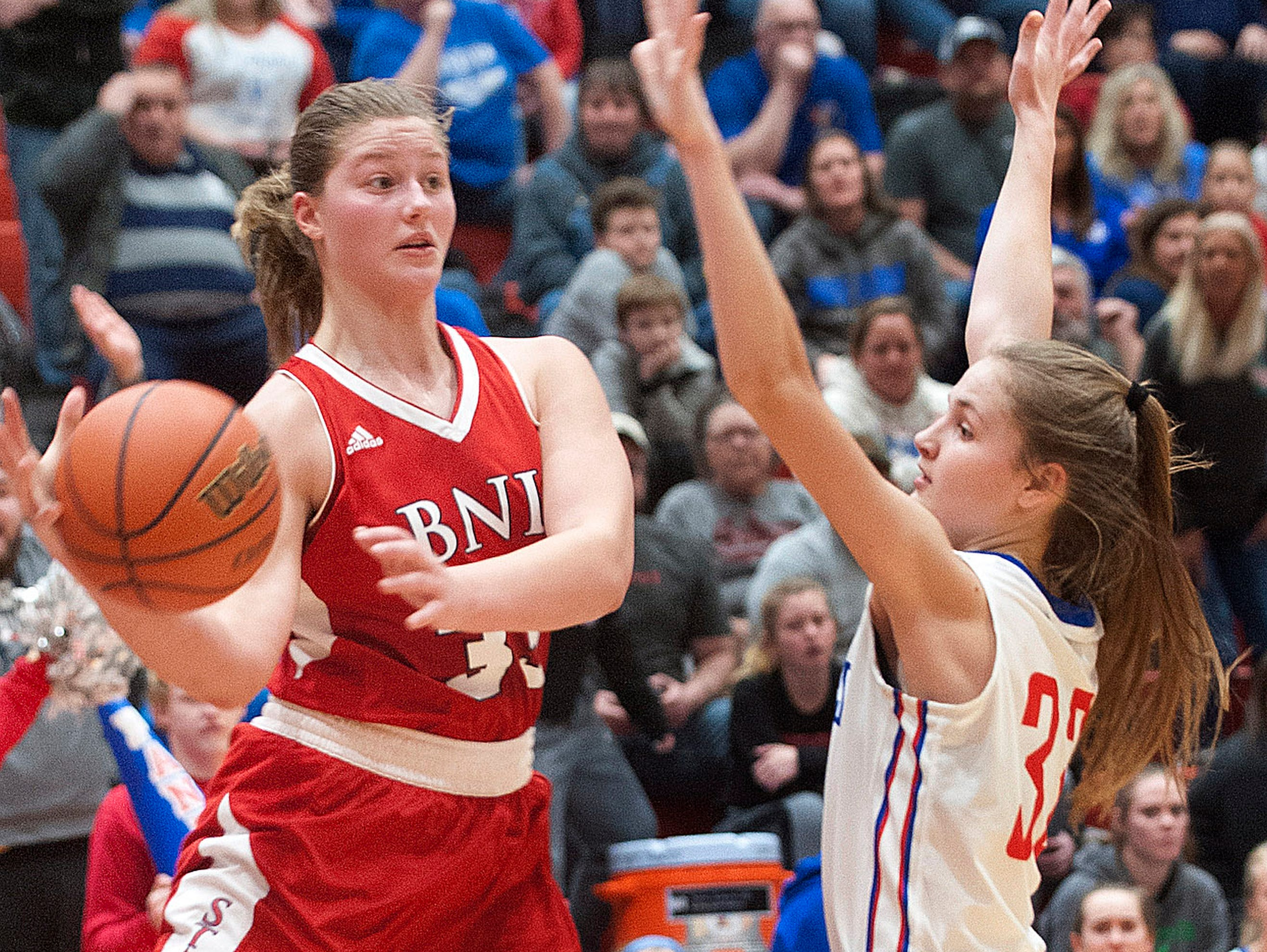 Bedford North Lawrence forward Jorie Allen looks to pass off as she is pressed by Jennings County guard-forward Lily Ernstes04 February 2019