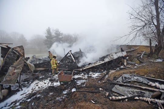 Firefighters sift through the remains of a barn fire on the property at 1491 Burnison Road early Tuesday morning.