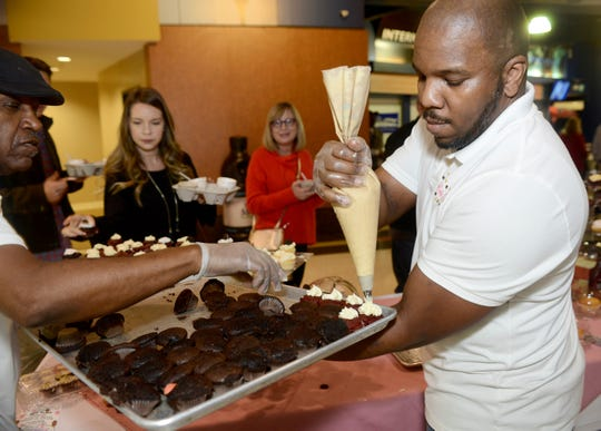 Workers with Cupcake Cutie Etc. put the final touches on their dessert offering at last year's Youth Villages Soup Sunday.