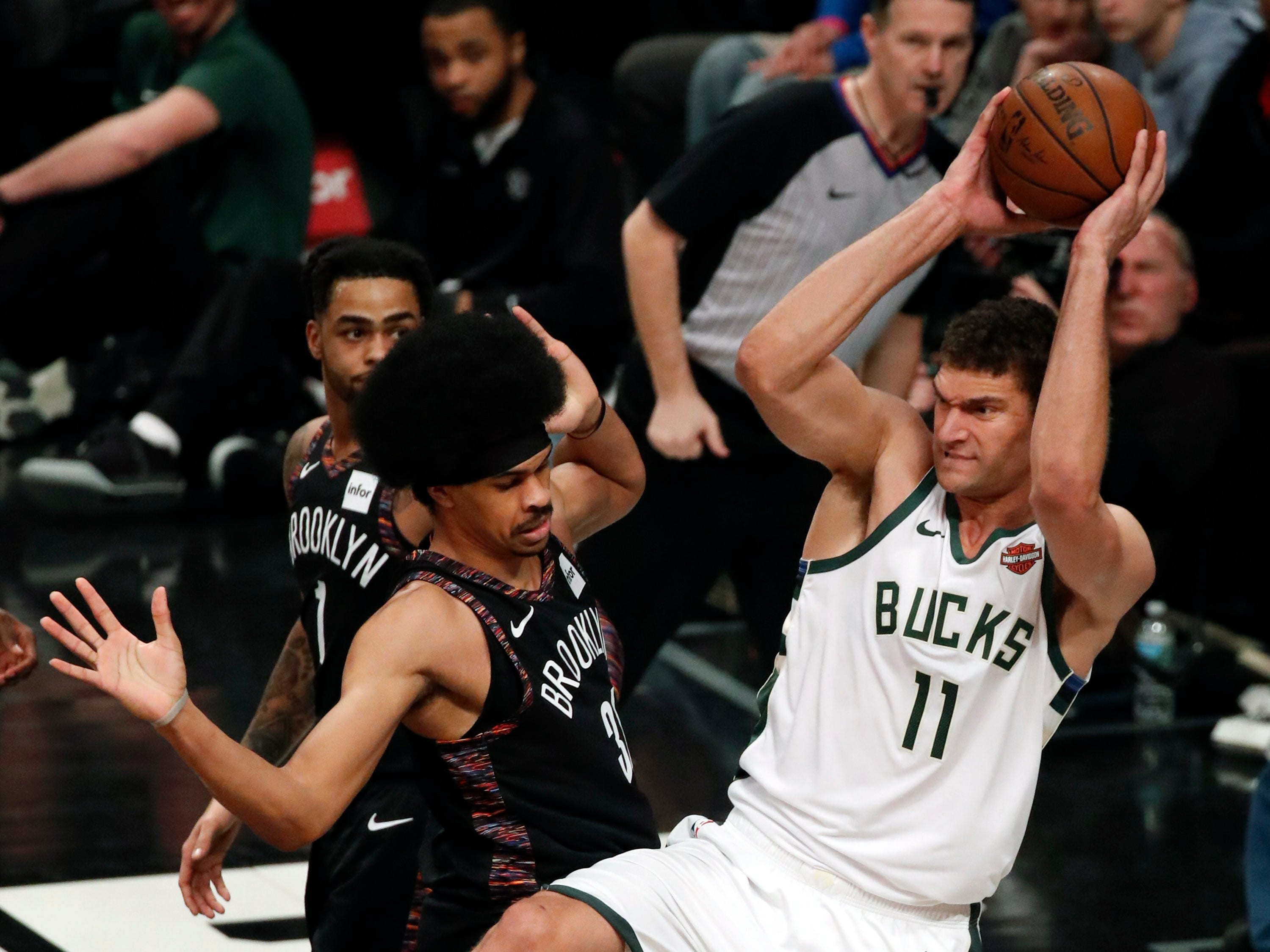 Bucks center Brook Lopez rips down a rebound in front of Nets center Jarrett Allen and gets ready to outlet to a teammate during the first half Monday.