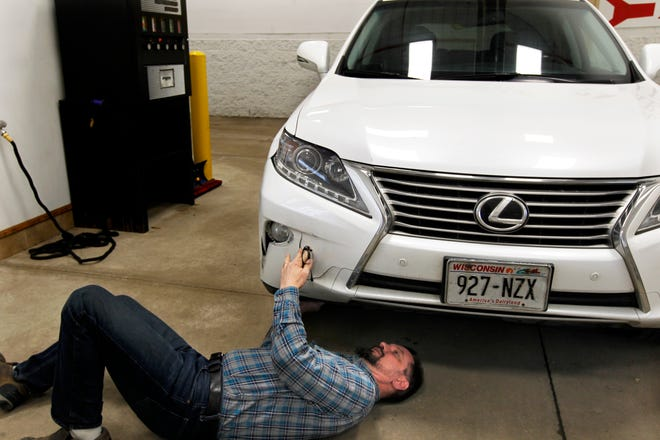 Steven Schulz performs an estimate on a car Tuesday at Pinkey's Capitol Auto Body in Milwaukee. The car was damaged from a snow bank.
