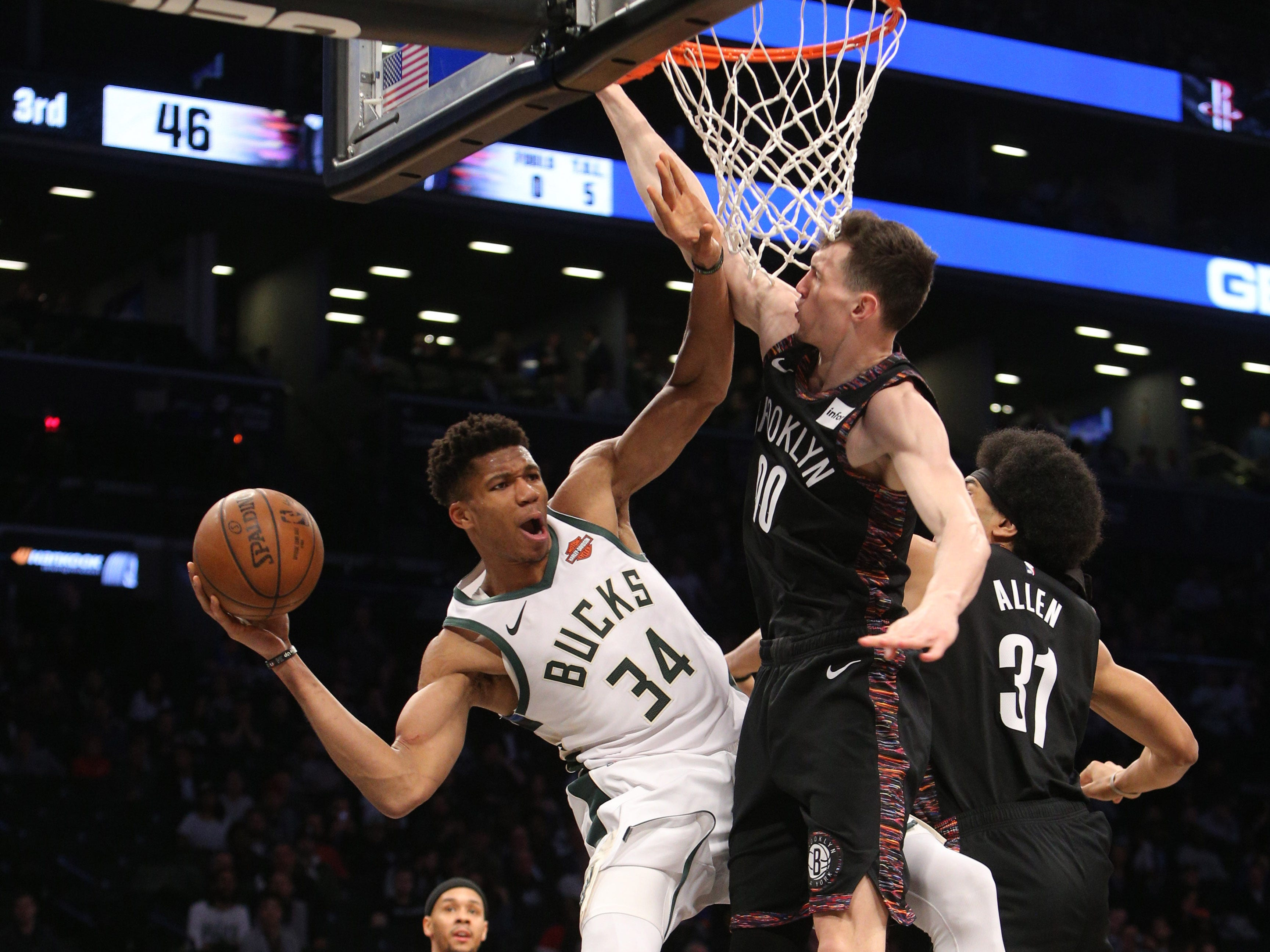 Bucks forward Giannis Antetokounmpo leans to his right side to whip a pass around Rodions Kurucs (center) and Jarrett Allen of the Nets during the third quarter Monday.