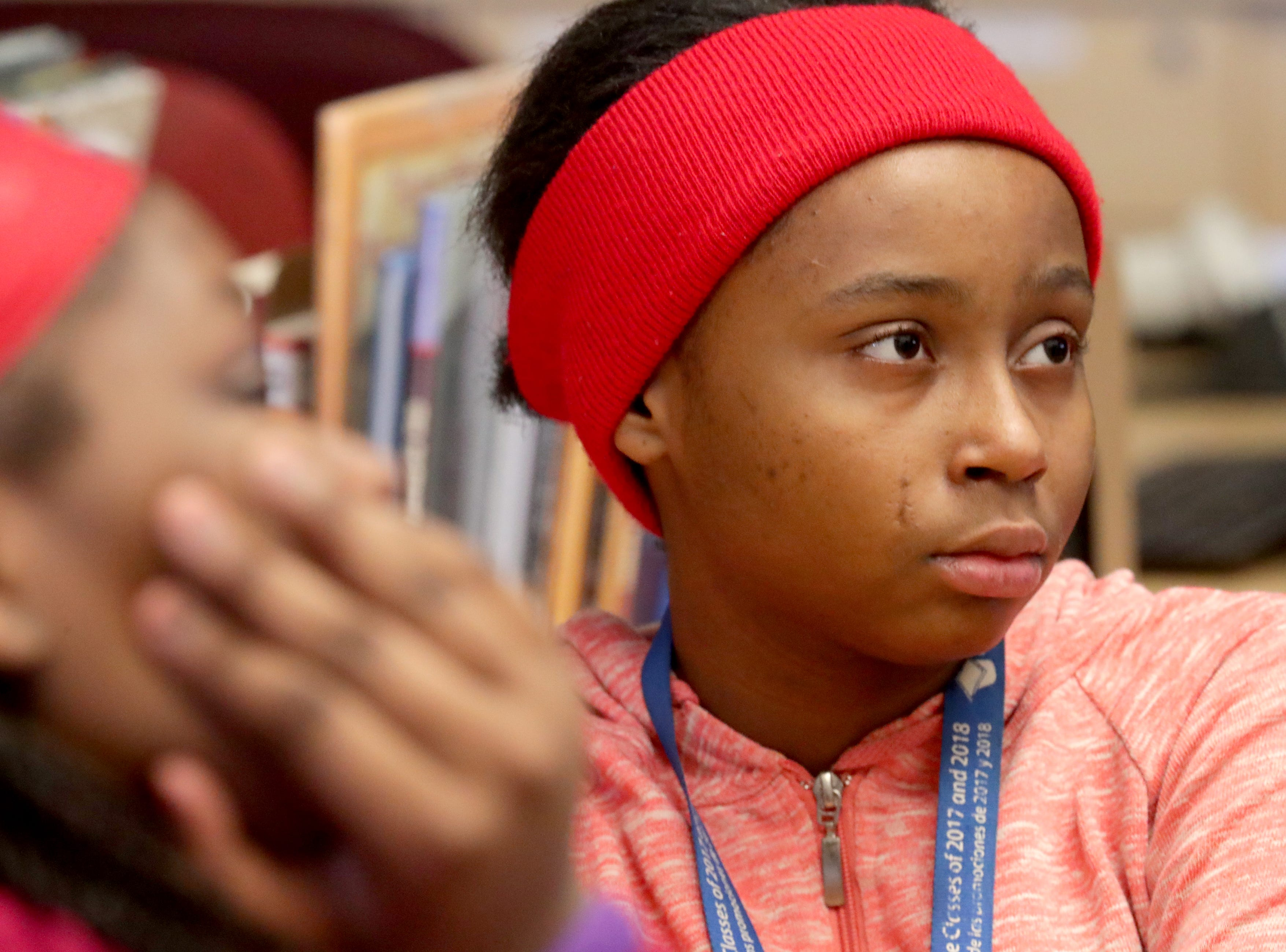 Eighth-grader Tatiana Edwards listens as Jerome Johnson, a library specialist speaks, to eighth-graders gathered in the library about the history of the equal rights movement.