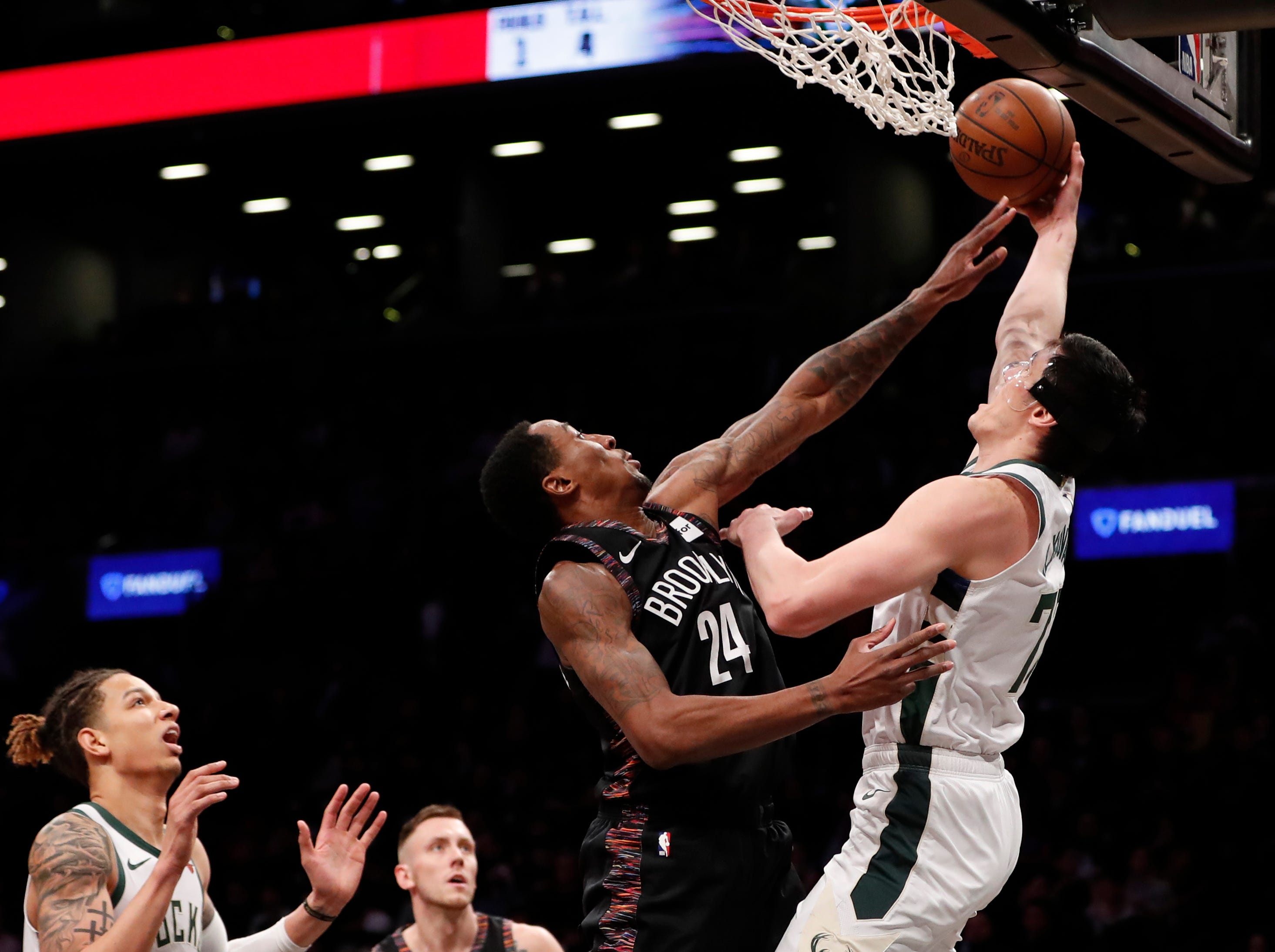 Bucks forward Ersan Ilyasova tries to get a shot over the block attempt of Nets forward Rondae Hollis-Jefferson during the second half Monday.