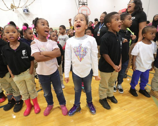 Kindergartners Ivionna Winston (center), Tamelah Christian (left of Winston) and Ezekiel Reed (right of Winston) recite the scholars' declaration at Martin Luther King Jr. elementary school on Monday