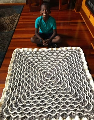 Jonah Larson shows off this gray afghan he crocheted.