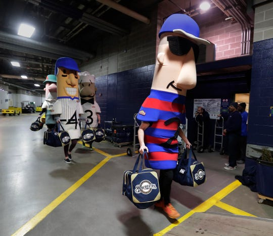 The Racing Sausages help carry baseball gear from the clubhouse to a semi-trailer at Miller Park.