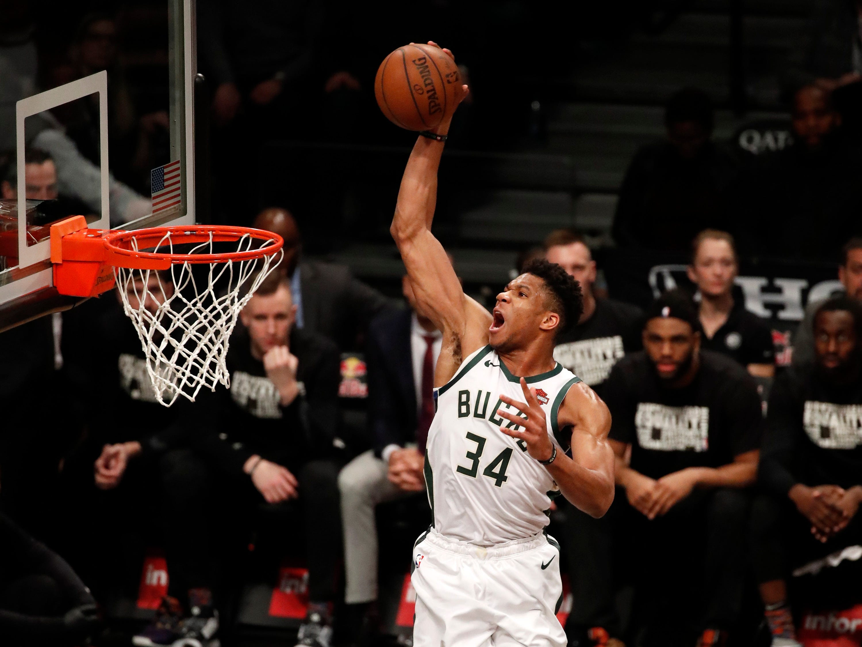 Bucks forward Giannis Antetokounmpo soars in for a dunk during the first half as Nets guard Treveon Graham can only look on.