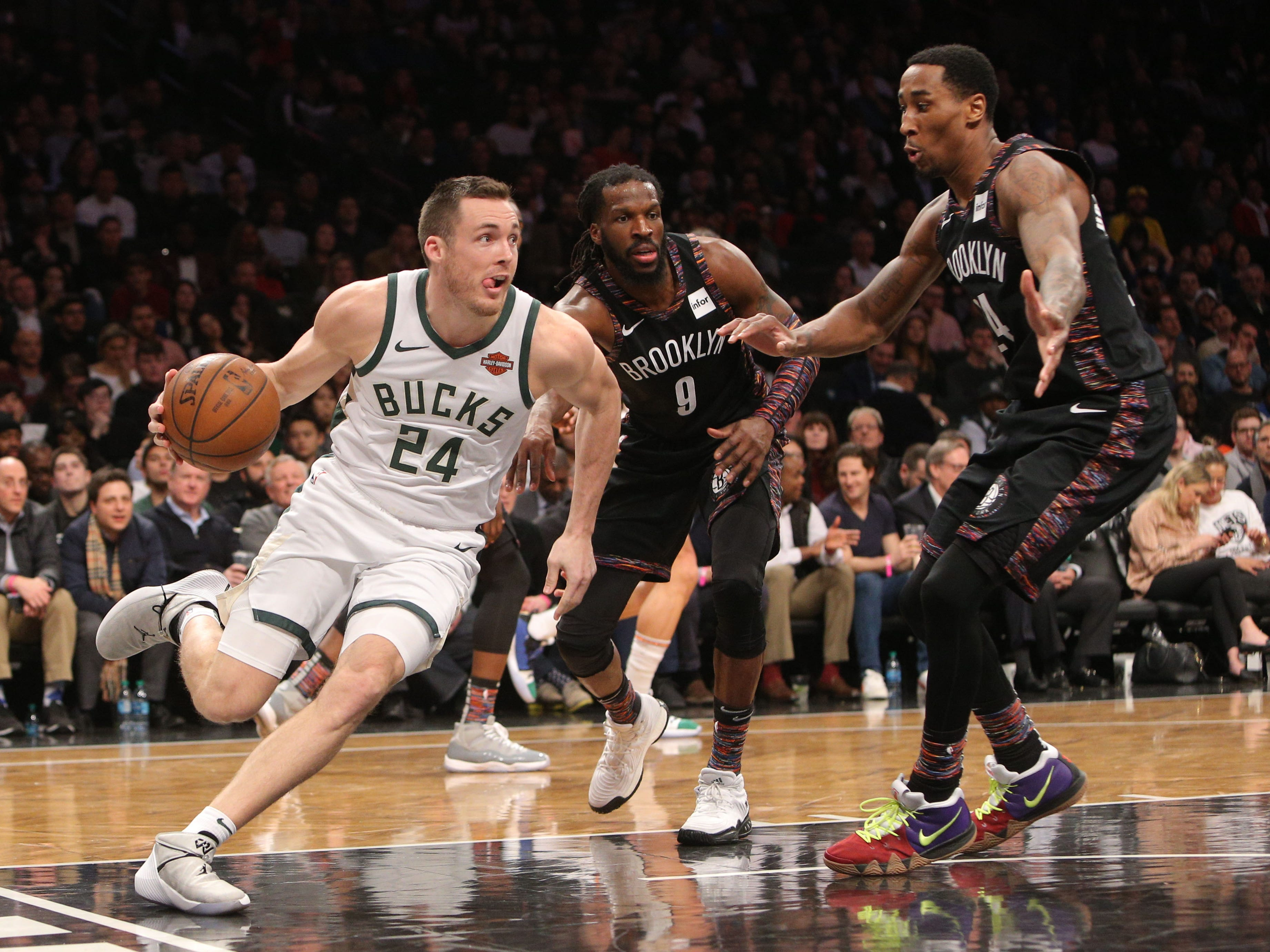 Bucks guard Pat Connaughton drives past DeMarre Carroll (center) and Rondae Hollis-Jefferson of the Nets along the baseline during the third quarter Monday.