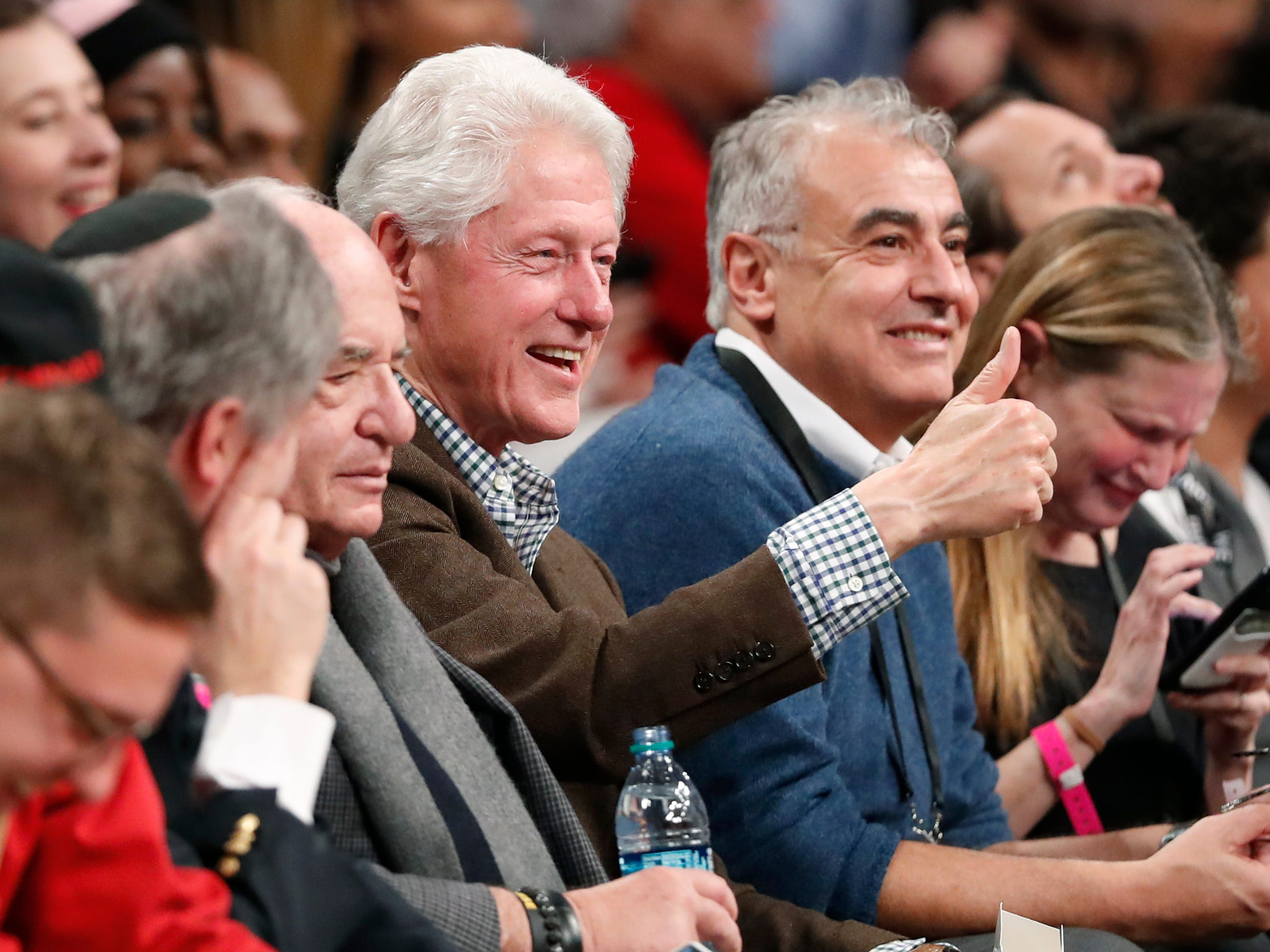 Former President Bill Clinton shoots someone a thumbs up as he sits courtside with Marc Lasry, one of the Bucks' principal owners, during Milwaukee's game against the Nets on Monday night in Brooklyn.