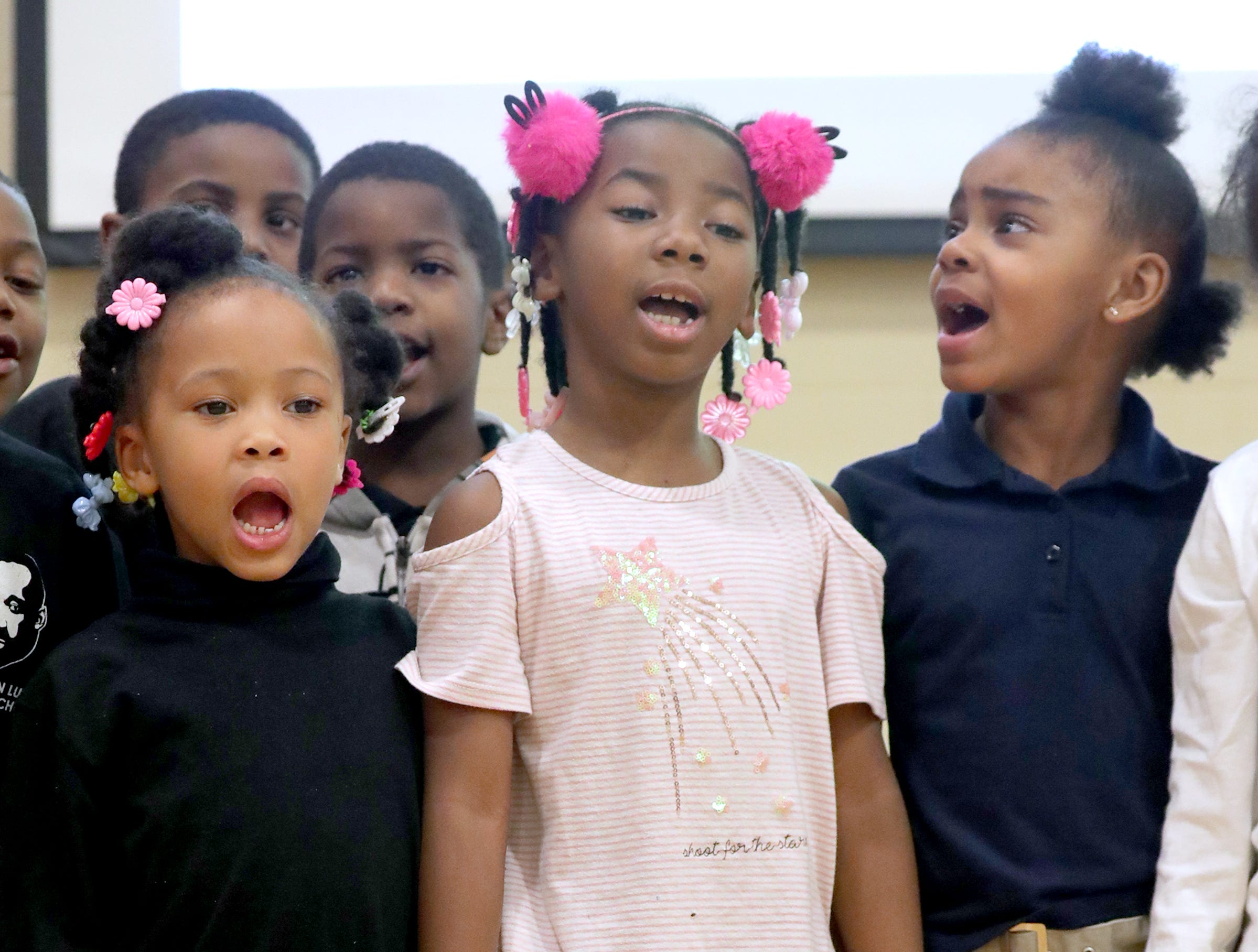 Students Tamelah Christian (center) holds hands with her fellow classmates while reciting the values of the school.