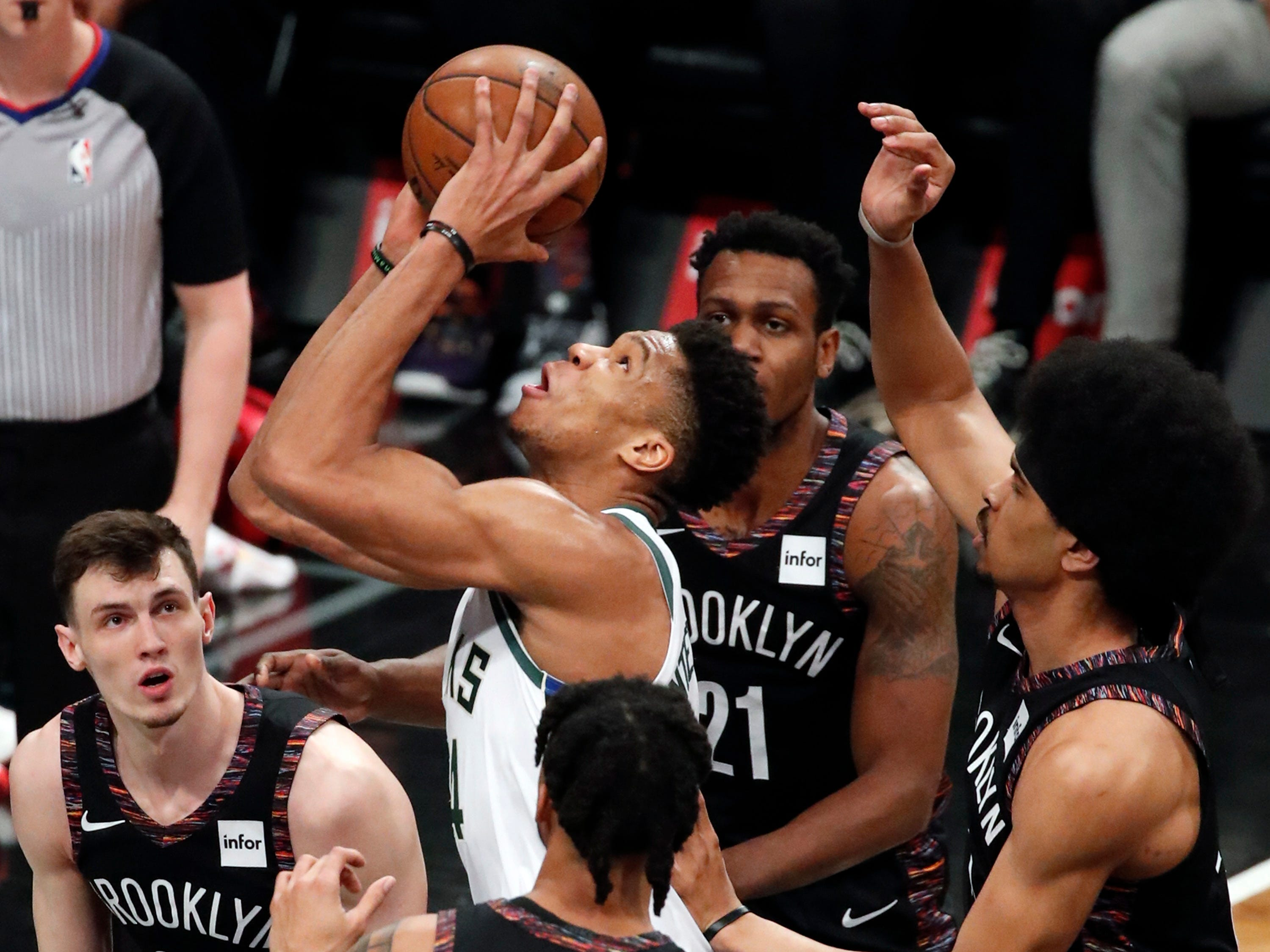 Bucks forward Giannis Antetokounmpo goes up for a shot down low despite being surrounded by a quartet of Nets players during the first half Monday.