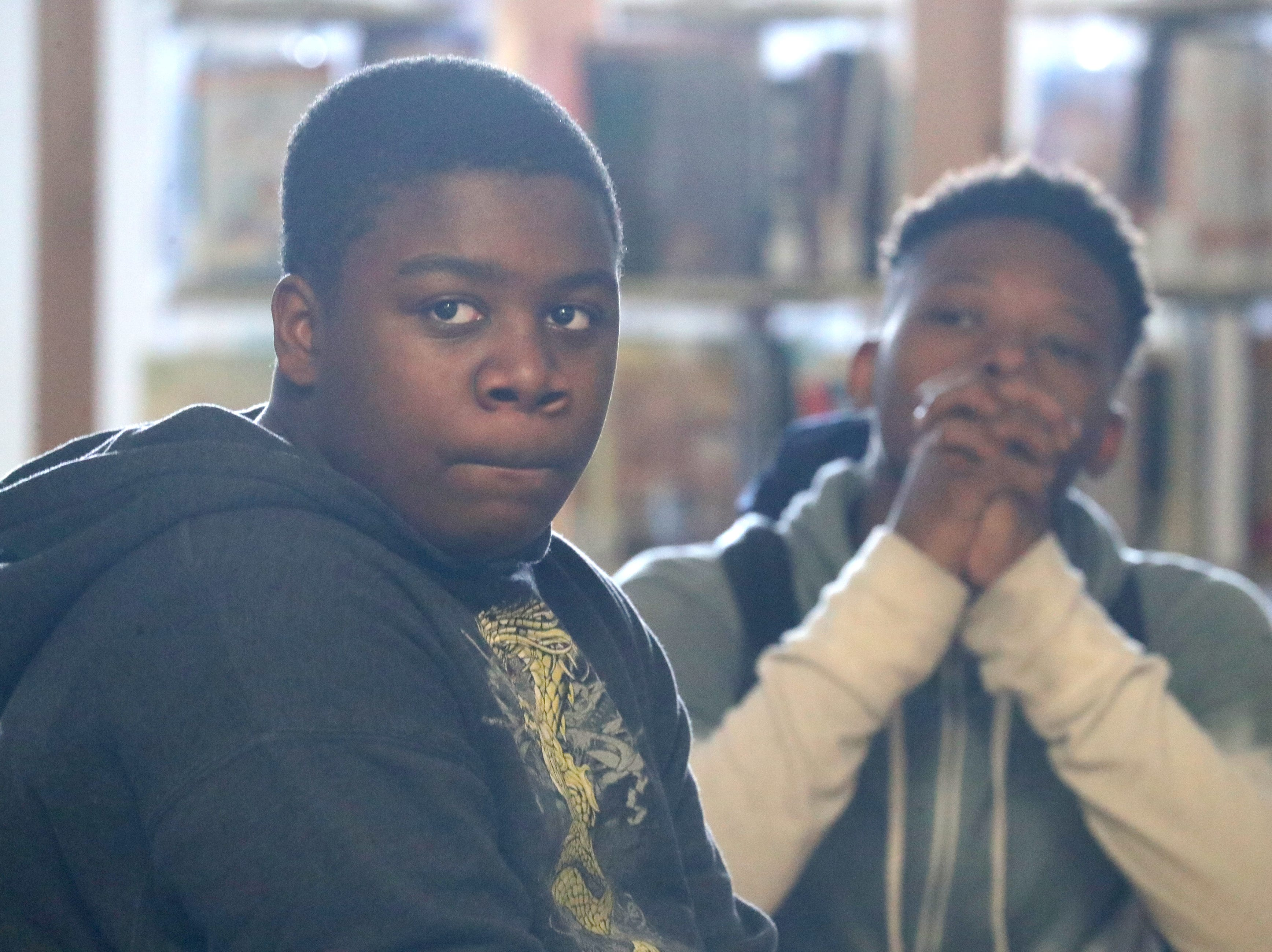 Eighth-graders Ladarius Dailey (left) and Kani Woolridge listen as Jerome Johnson a library specialist, speaks about the history of the equal rights movement.