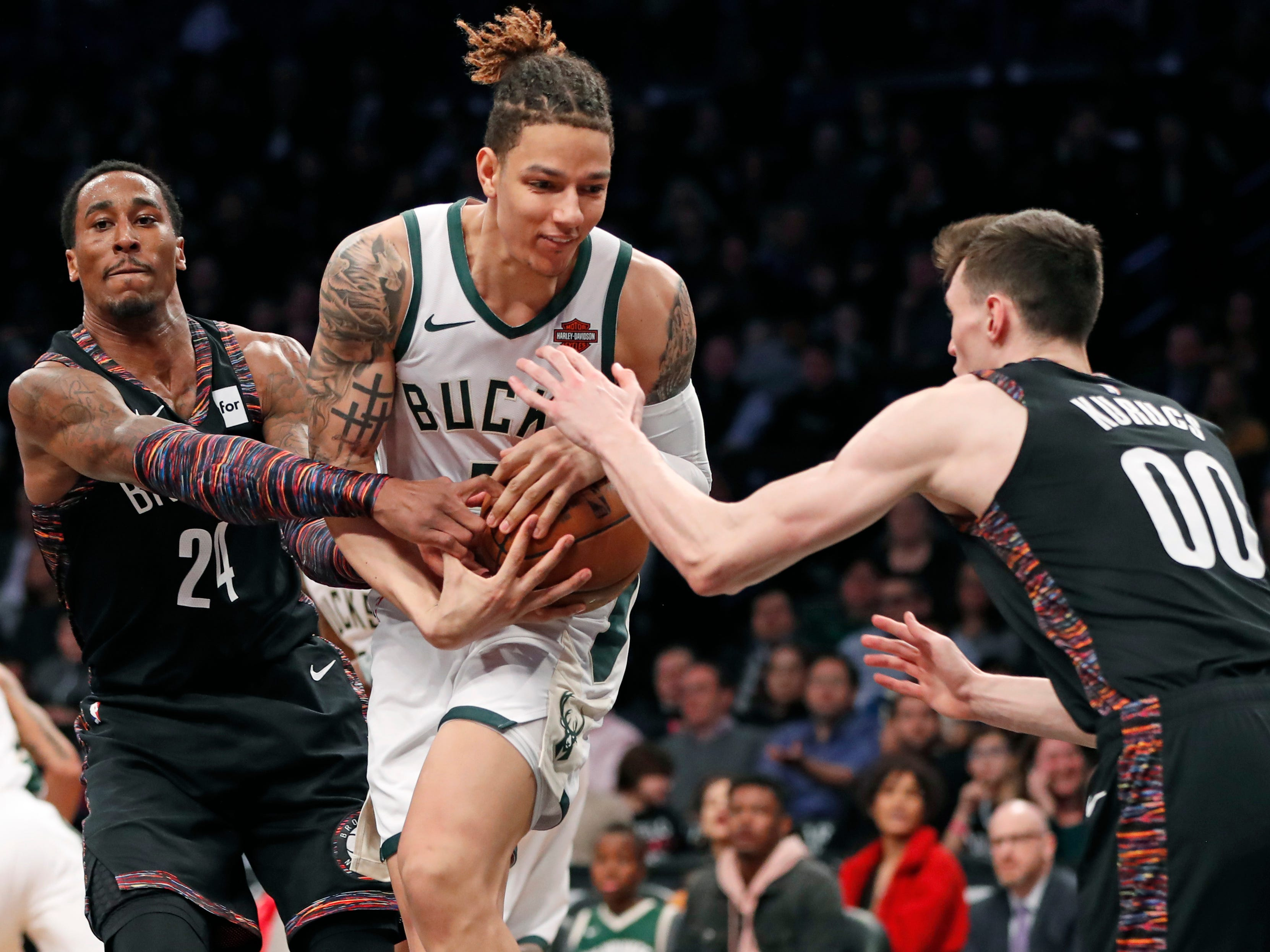 Bucks forward D.J. Wilson protects the ball as Rondae Hollis-Jefferson (left) and  Rodions Kurucs of the Nets try to rip it away during the first half Monday night.