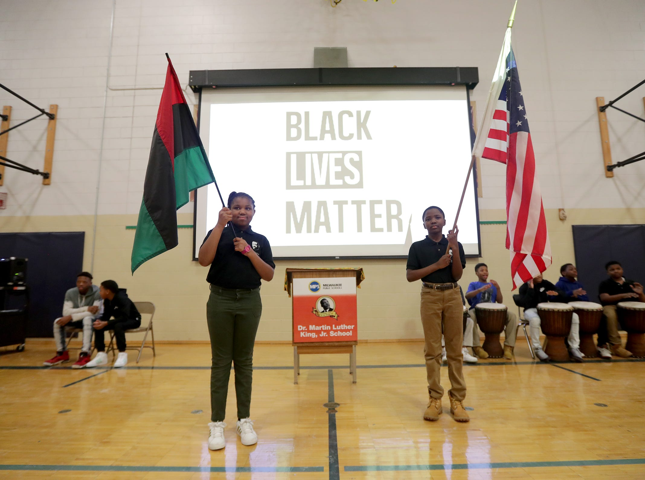 Martin Luther King Jr. Elementary fourth-graders Taviana Smith (left) and Demaris Easley stand Monday with an African-American flag and an American flag during a morning assembly, called a Mbongi, the school at 3275 N. King Drive in Milwaukee. Dr. Martin Luther King Jr. Elementary  is Milwaukee's only African-American Immersion school. While area schools are celebrating Black Lives Matter Week this week, at Dr. Martin Luther King Jr. Elementary, it's Black Lives Matter every day.