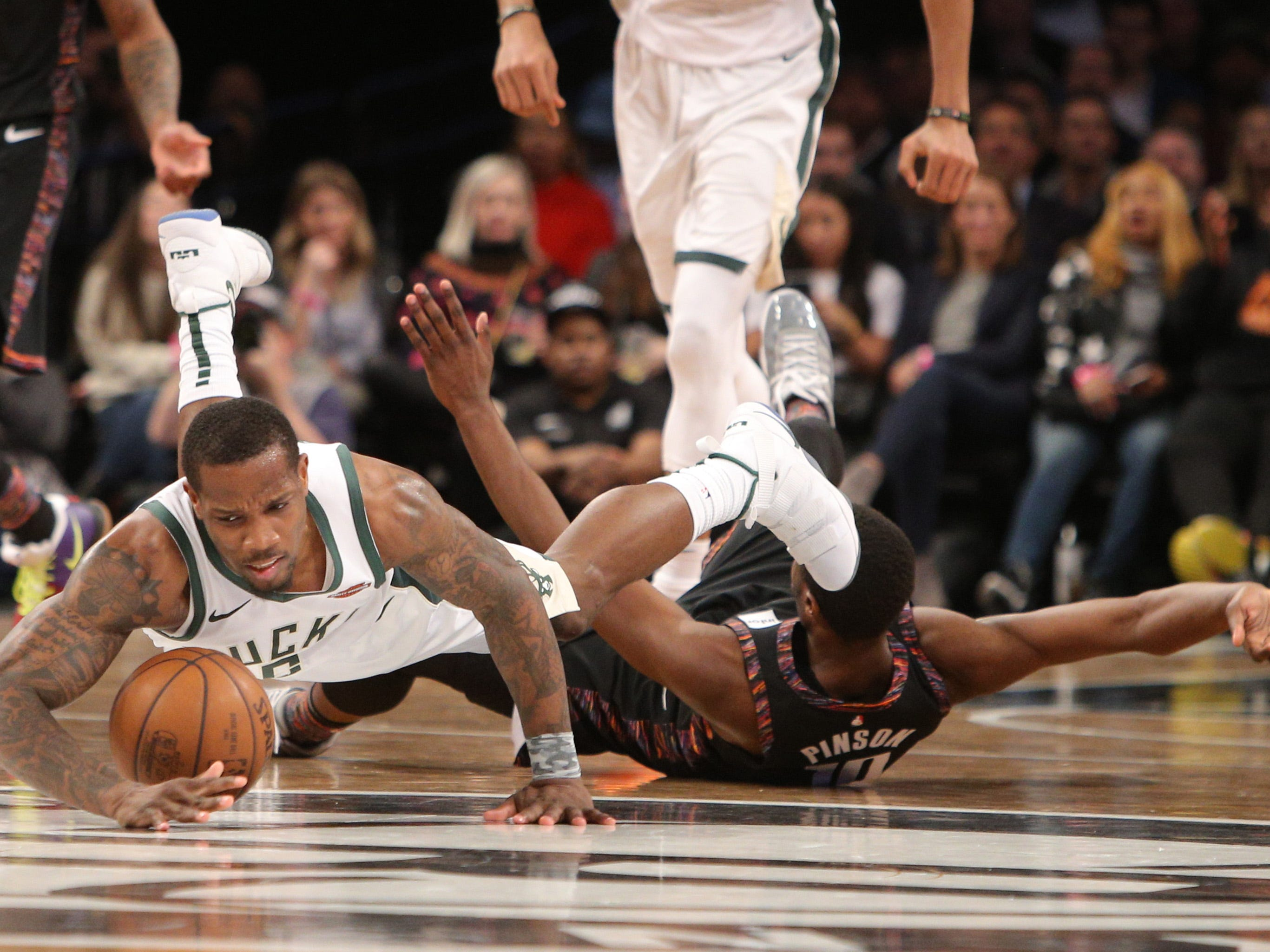 Bucks guard Eric Bledsoe is fouled after getting to a loose ball a click quicker than Nets guard Theo Pinson during the fourth quarter Monday night.