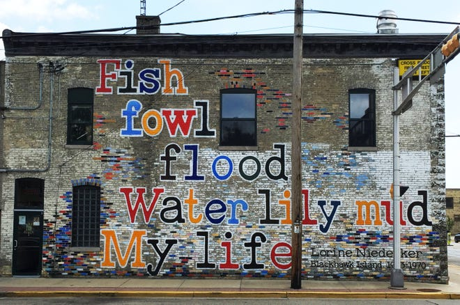 """People driving through downtown Fort Atkinson can see the opening words of Lorine Niedecker's """"Paean to Place"""" on the exterior wall of a building."""