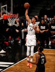 Bucks forward Giannis Antetokounmpo soars to the basket for a dunk as Nets guard Treveon Graham can only watch during the first half on Monday night.
