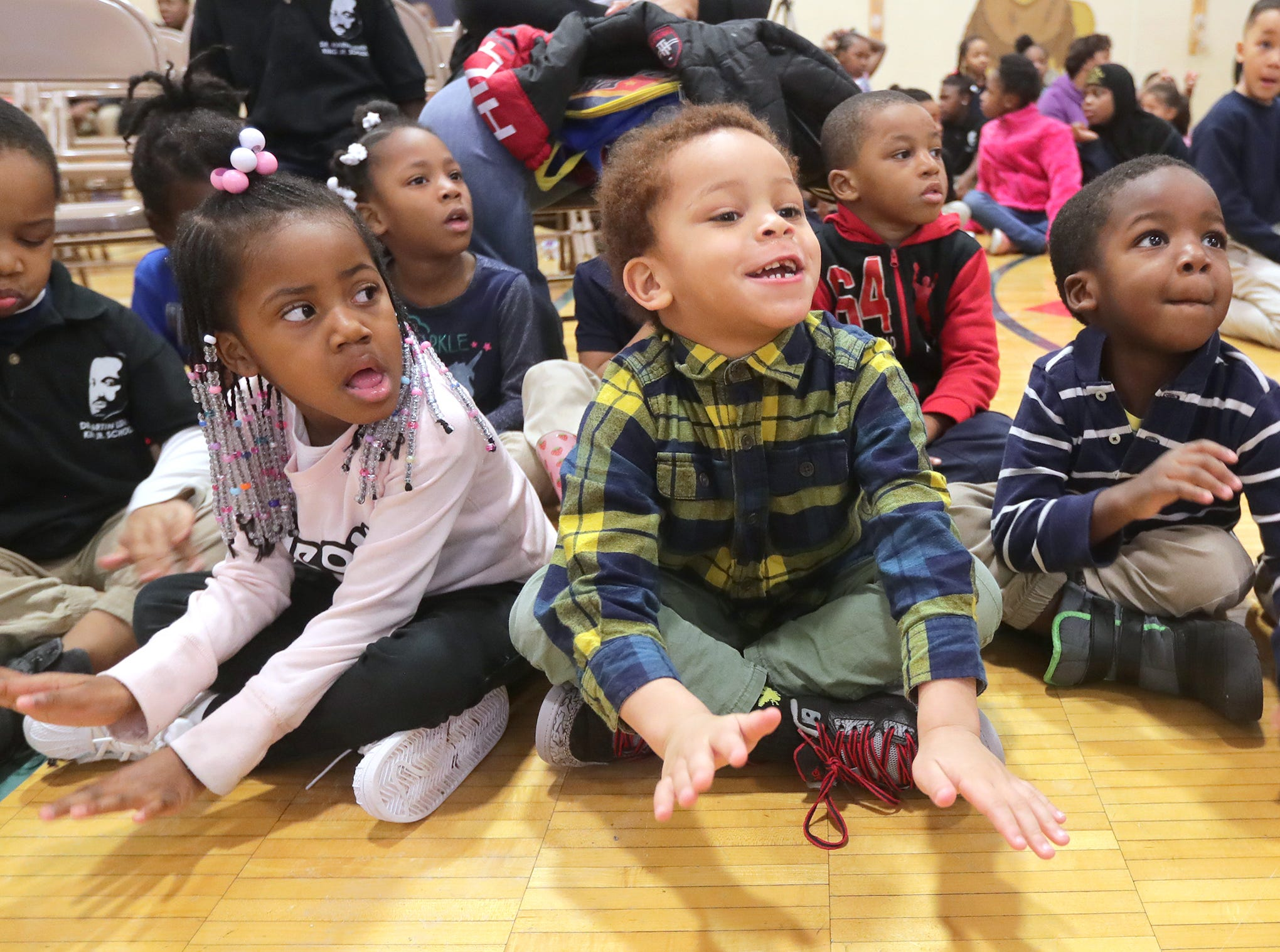 Dr. Martin Luther King Jr. Elementary 4K students Kamiya Young (from left), Terrence Henderson and Jareco Wright listen to a musical performance during the morning assembly.