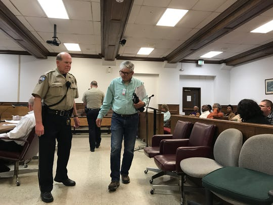 A Guard escorts architect Tommy Hatten from the Ouachita Parish Police Jury meeting on Monday night.