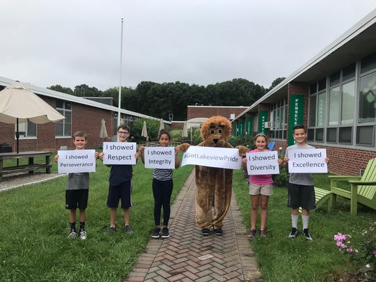 Lakeview Elementary School students stand with the school's lion mascot, whose sign shows the hashtag that helped their effort in kindness go viral in Denville.