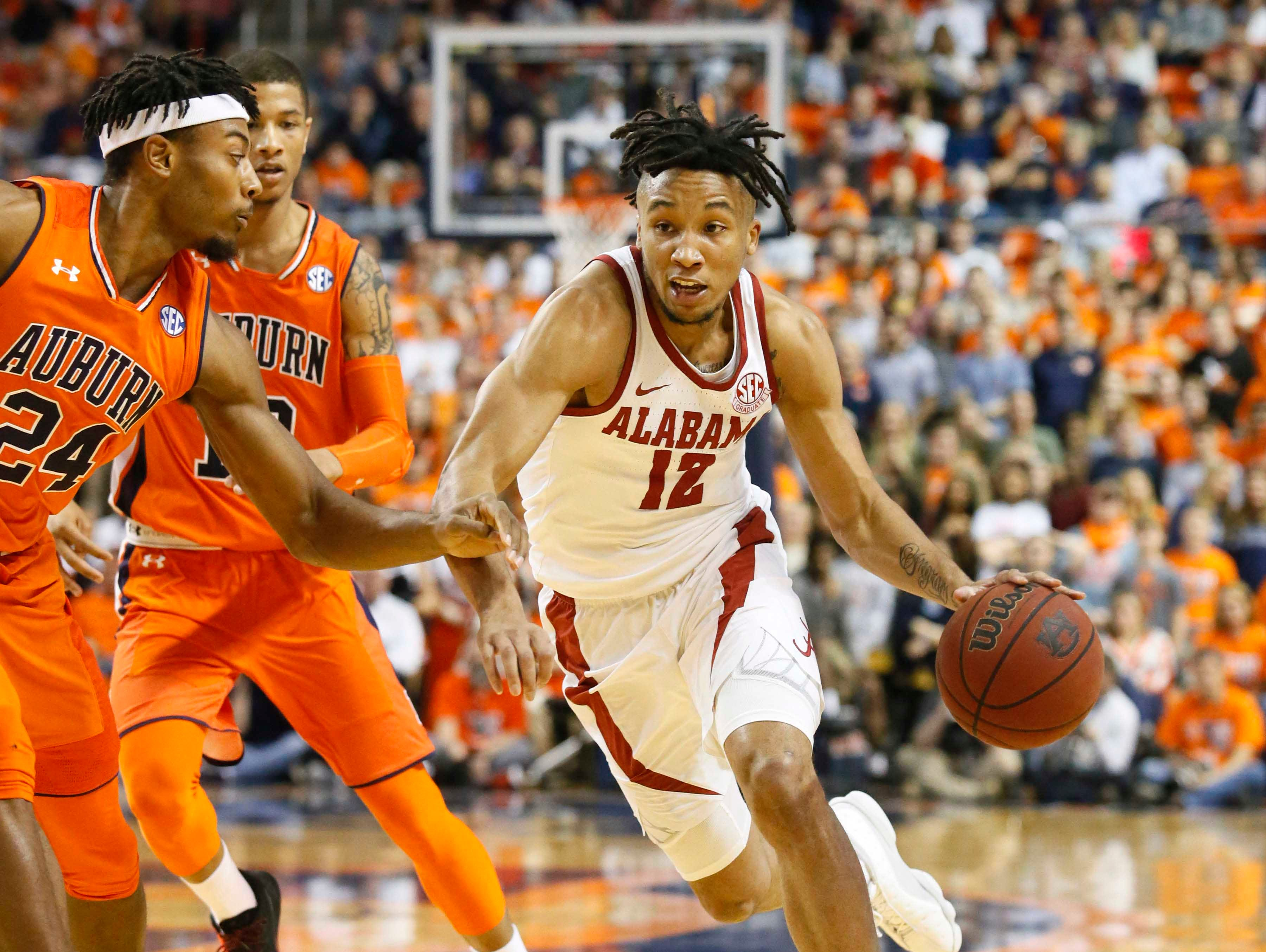 Feb 2, 2019; Auburn, AL, USA; Alabama Crimson Tide guard Dazo Ingram (12) drives against Auburn Tigers forward Anfernee McLemore (24) during the first half at Auburn Arena. Mandatory Credit: John Reed-USA TODAY Sports