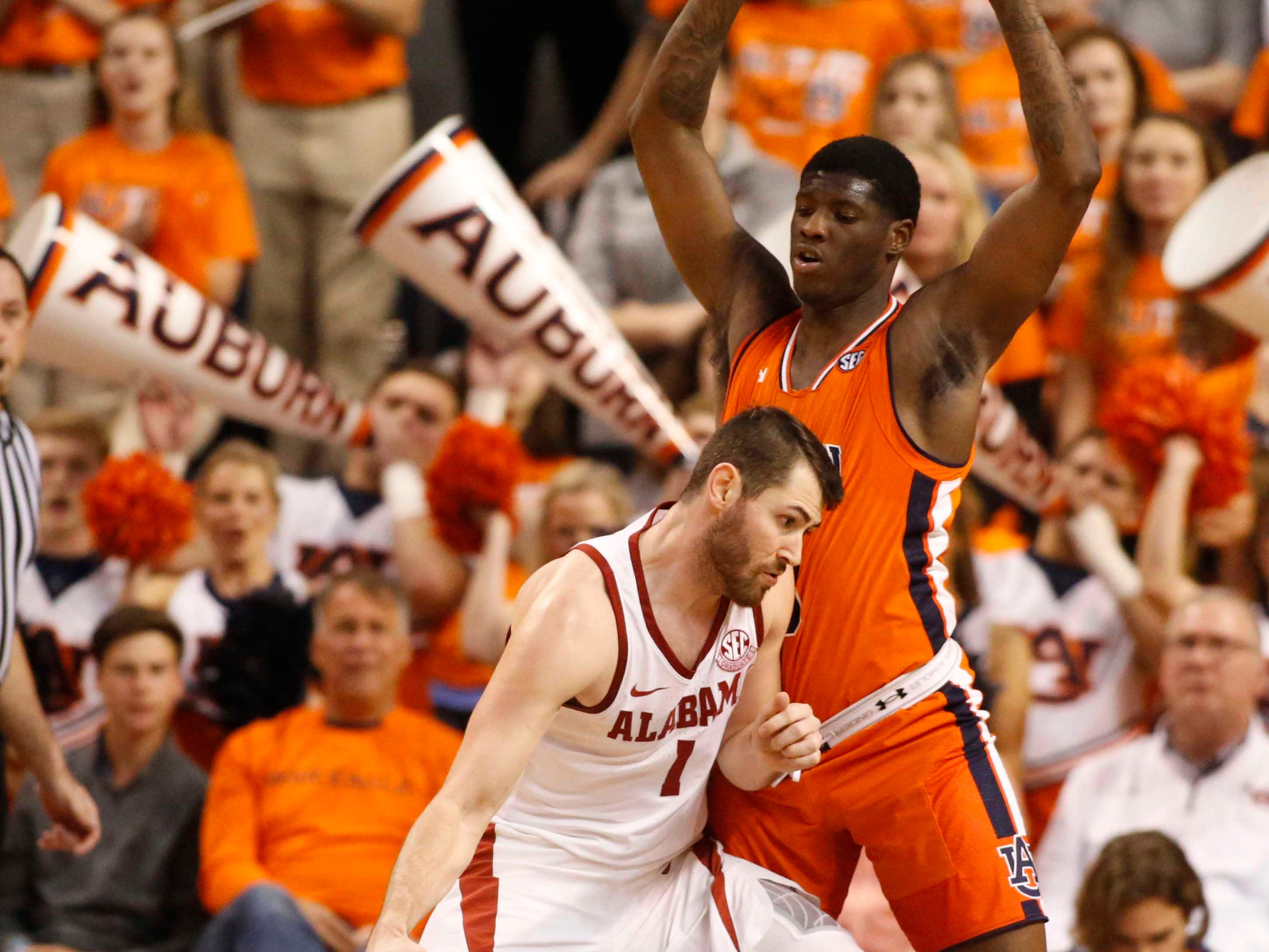Feb 2, 2019; Auburn, AL, USA; Alabama Crimson Tide guard Riley Norris (1) is blocked by Auburn Tigers forward Daniel Purifoy (3) during the second half at Auburn Arena. Mandatory Credit: John Reed-USA TODAY Sports