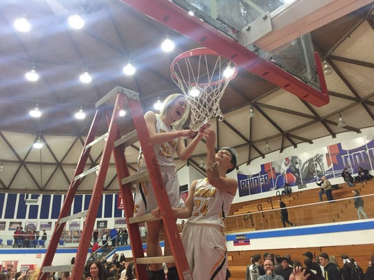 Cowan's Elizabeth Clevenger cuts the net with the help of teammate Payton Maher after the Blackhawks won their first sectional title in program history.