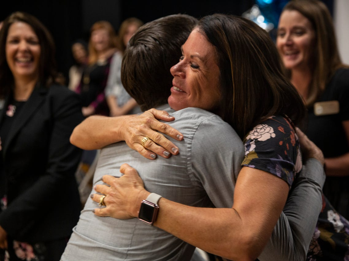 "Leslie Gunderson hugs her coworker, social worker Paul Milford, after Milford was suprised with the ""School-related Employee of the Year"" award at Bonita Springs Middle School in Bonita Springs on February 5, 2019."