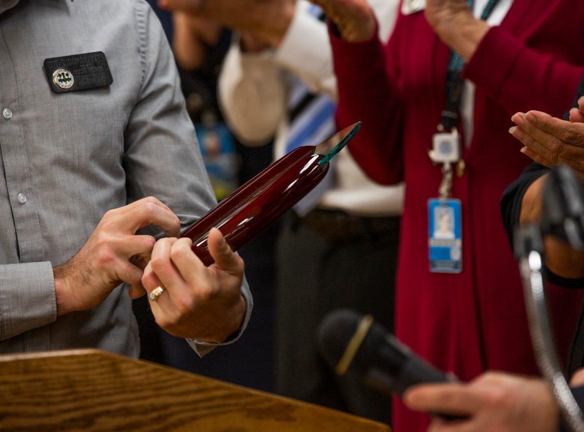 Social worker Paul Milford looks at his award at Bonita Springs Middle School in Bonita Springs on February 5, 2019.
