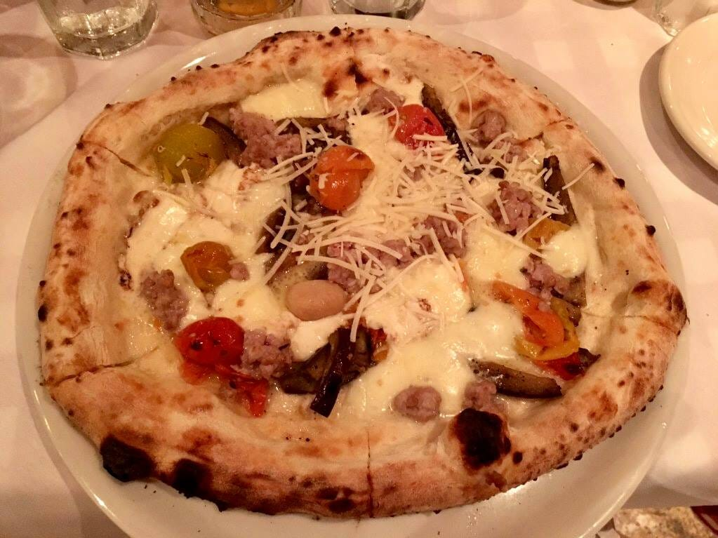 The rustica is a white pizza at La Trattoria in downtown Naples strewn with Italian sausage, slivers of eggplant,  cherry tomatoes and smoked scamorza cheese.