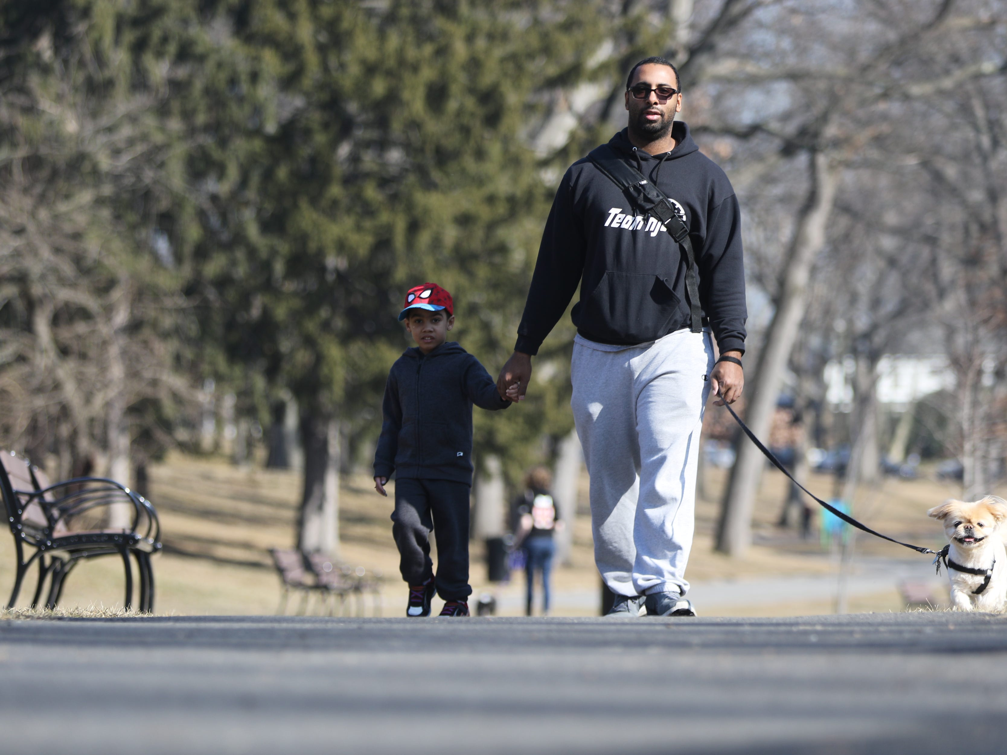 Julian Belizaire (center) walks with his son, Joshua Belizaire, three, and their dog, Tyson, at Third Ward Park, in Passaic. Temperatures reached the mid 60's, Tuesday, February 5, 2019.