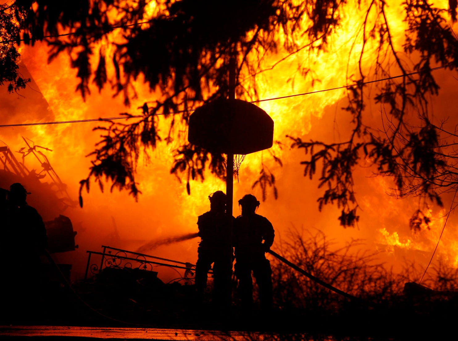 Volunteer firefighters attempt to put out the flames from Continental Airlines Flight 3407 on Thursday Feb. 12, 2009 after it crashed into a home in Clarence Center, N.Y. killing all 48 people on board and one on the ground according to officials. (AP Photo/The Buffalo News - Harry Scull Jr)