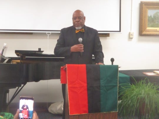 Howard Fulcher addresses the audience at the African-American Heritage Month celebration held at the main branch of the Paterson Public library.