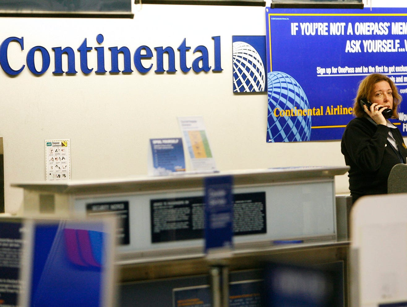 A Continential Airlines employee talks on the phone at  the Buffalo Niagara Airport on Thursday Feb. 12, 2009 after Continental Airlines Flight 3407 crashed into a home in Clarence Center, N.Y. killing all 48 people on board and one on the ground according to officials.