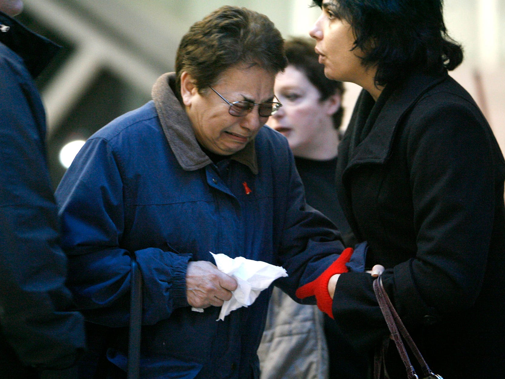 """""""Family members leave the Buffalo Niagara Airport on Thursday, Feb. 12, 2009 after Continental Airlines Flight 3407 crashed into a home in Clarence Center, N.Y. A commuter plane """"""""basically dove"""""""" into a house while coming in for a landing, sparking a fiery explosion that killed all 48 people on board and one person on the ground, an emergency official said Friday. (AP PHOTO/The Buffalo News,Harry Scull Jr)"""""""