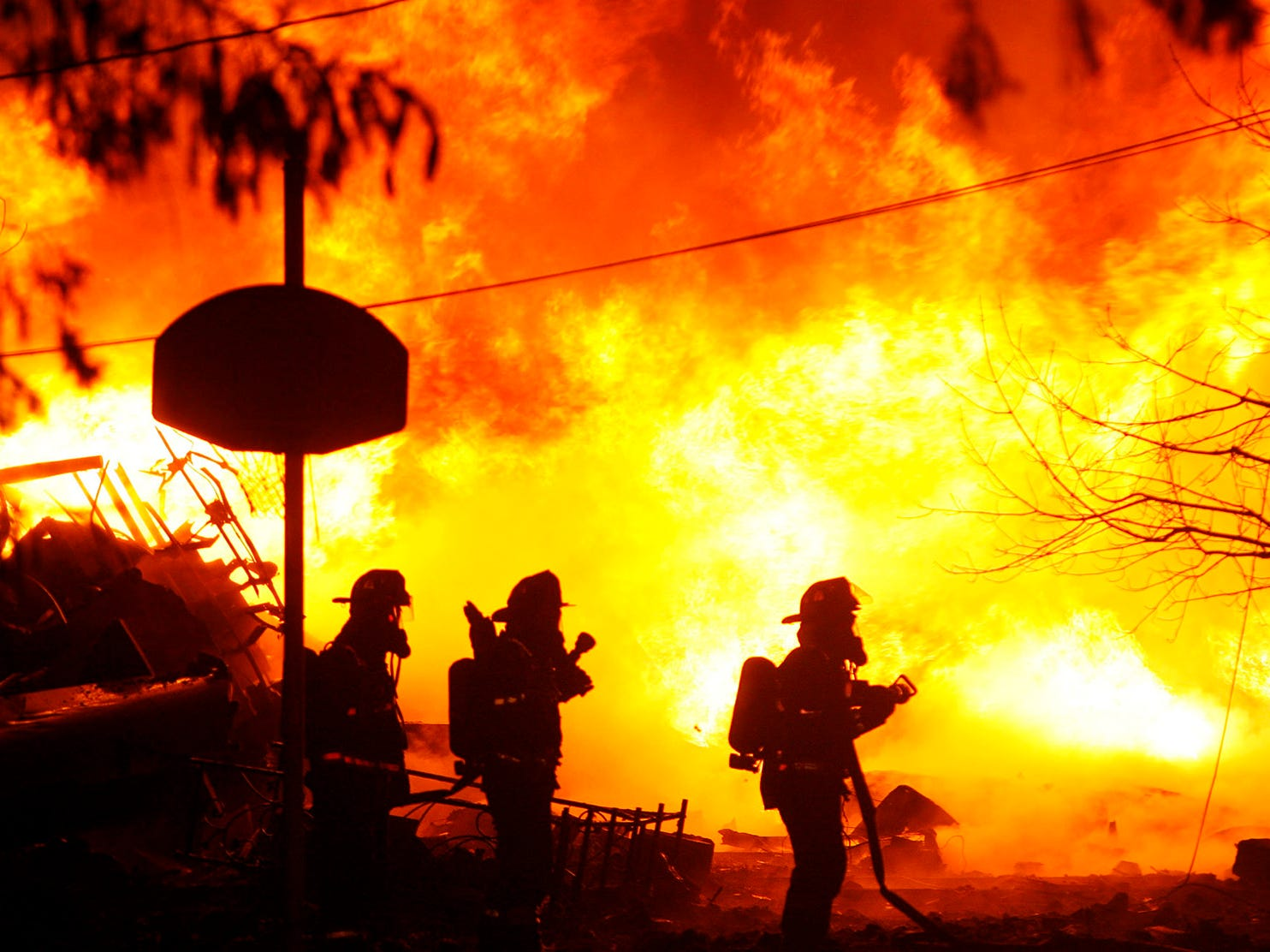 Volunteer firefighters attempt to put out flames from Continental Airlines Flight 3407  on Thursday Feb. 12, 2009 after it crashed into a home in Clarence Center, N.Y. killing all 48 people on board and one on the ground according to officials. (AP Photo/The Buffalo News - Harry Scull Jr)
