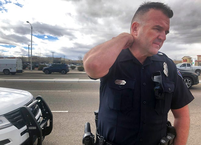 Officer Simon Drobik answers questions about an explosion that he says killed one person in Albuquerque, N.M., on Monday, Feb. 4, 2019. Police say they are investigating the explosion that happened in an alley behind a strip mall with a grocery store, pharmacy and several other businesses.