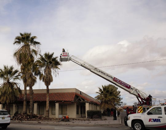 The Las Cruces Fire Department extends a ladder and bucket carrying two firefighters on Tuesday, Feb. 5, 2019 to rescue a tree trimmer who got trapped in a tall palm tree at a strip mall on Idaho Avenue. The man was successfully rescued.