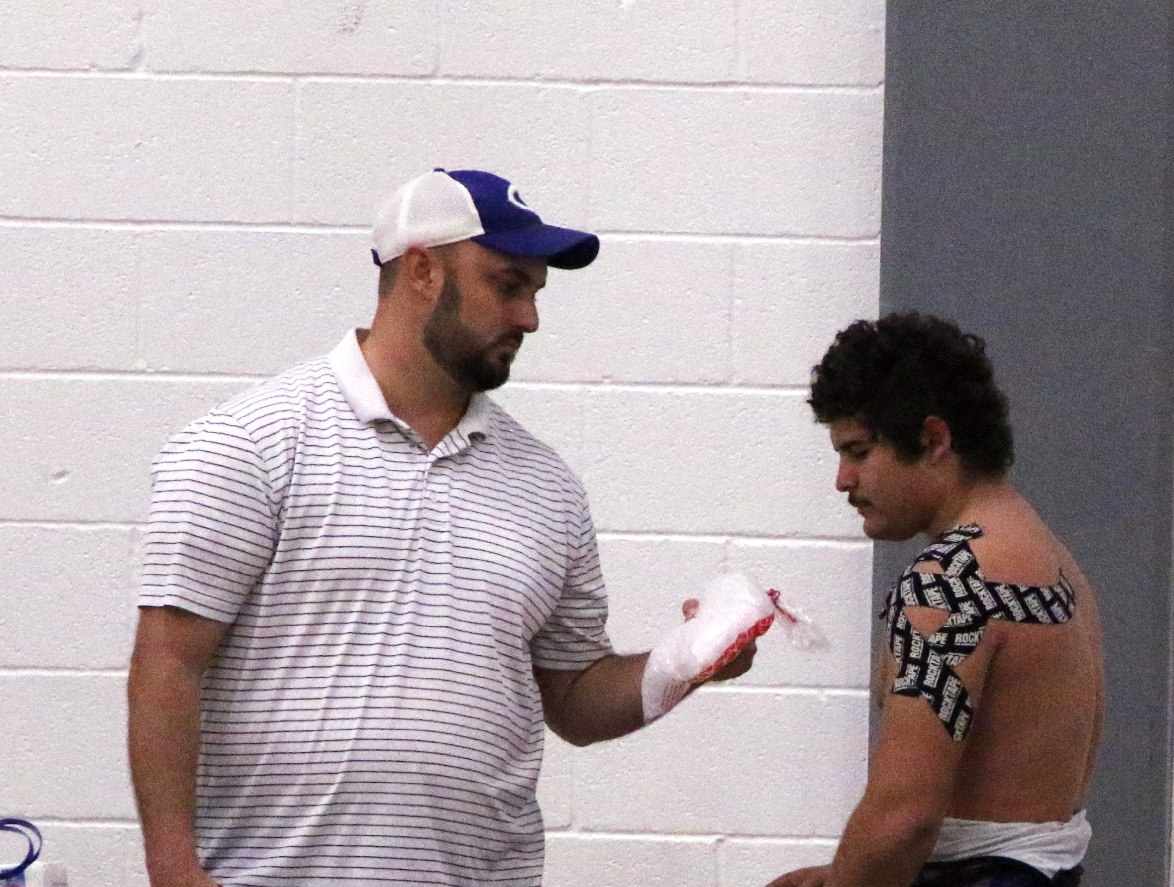 RJ Baca talks to Carlsbad's trainer about ice treatment after he won his match in Saturday's district dual against Alamogordo.