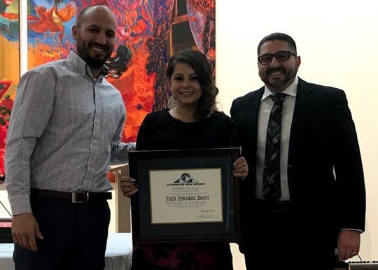 Ekta Patel, center, of Carlsbad, receives a graduation certification from Leadership New Mexico.