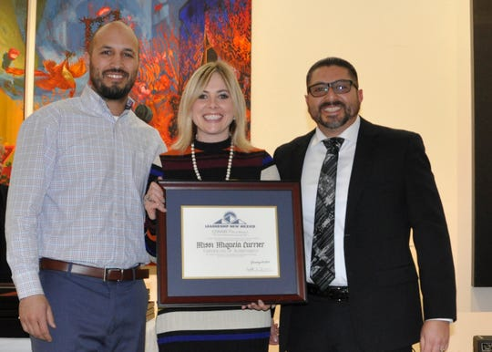 Missi Currier, center, receives a graduation certification from Leadership new Mexico.
