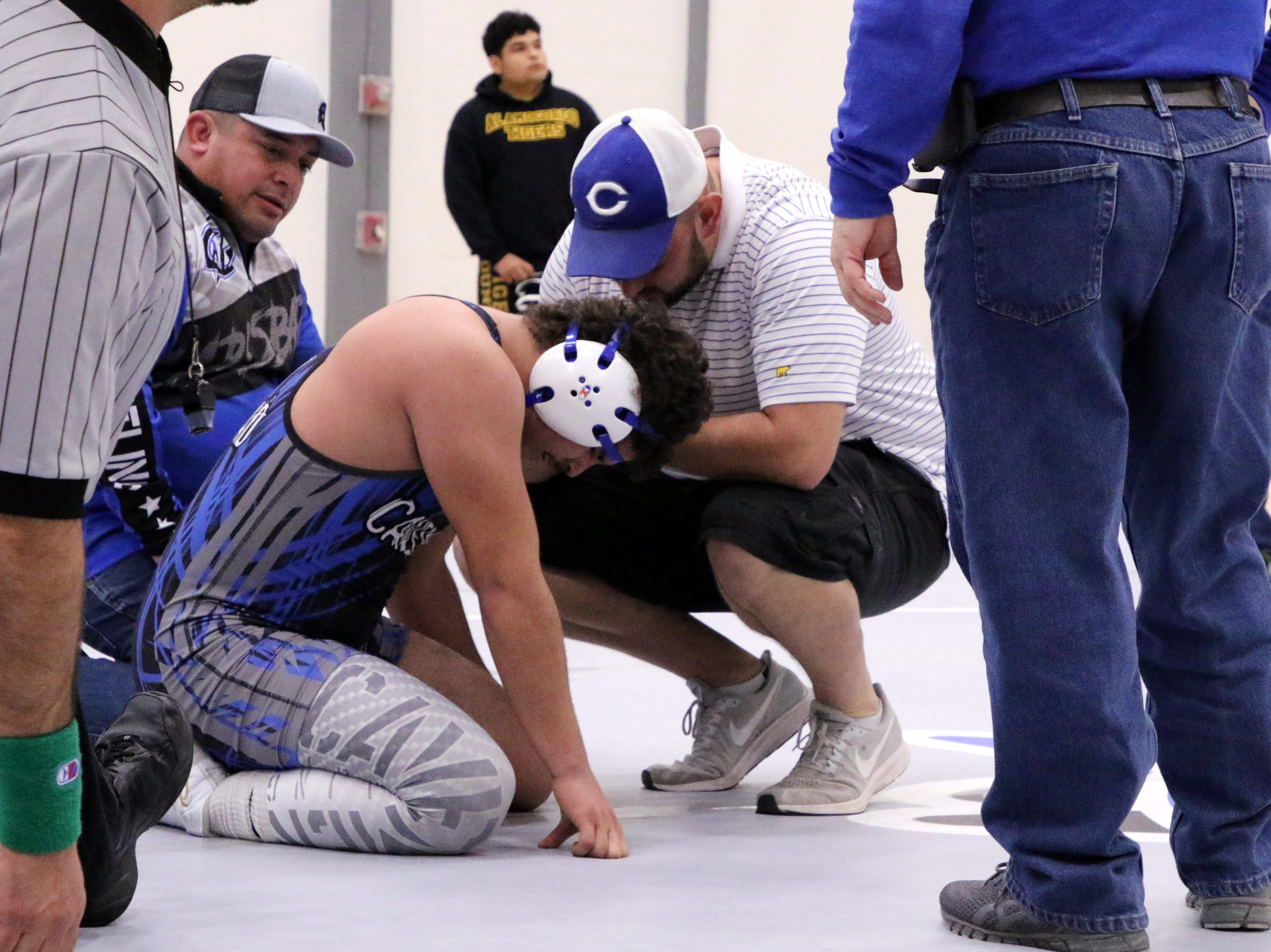 RJ Baca is seen by trainers, right, and coaches, left, to check out his injured left shoulder during Saturday's district dual against Alamogordo. He finished the match and got a pinfall victory.