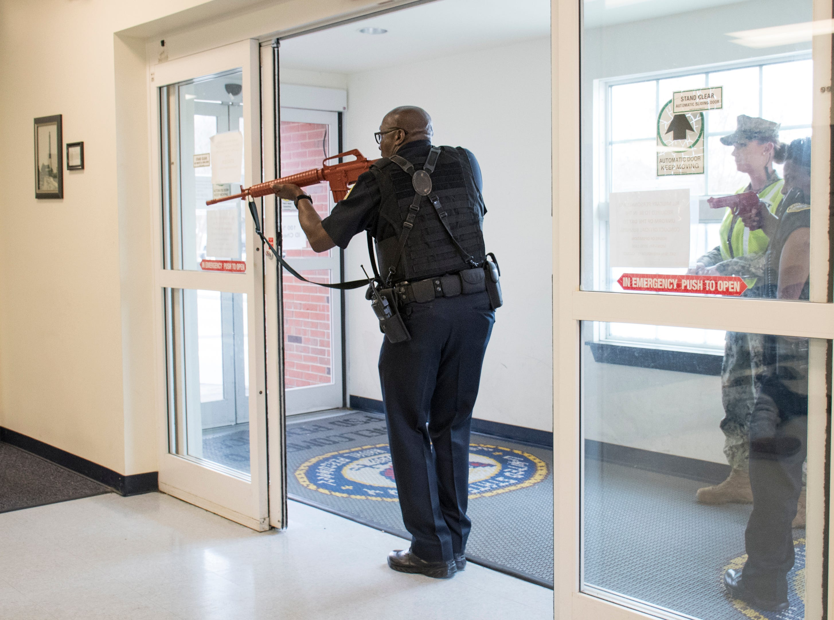 NAS Pensacola Police Officers Samuel Watkins, left, and Sophia Barnes enter the Personnel Support Detachment building during Exercise Solid Curtain-Citadel Shield, an annual security exercise is conducted at NAS Pensacola on Tuesday, February 4, 2019.