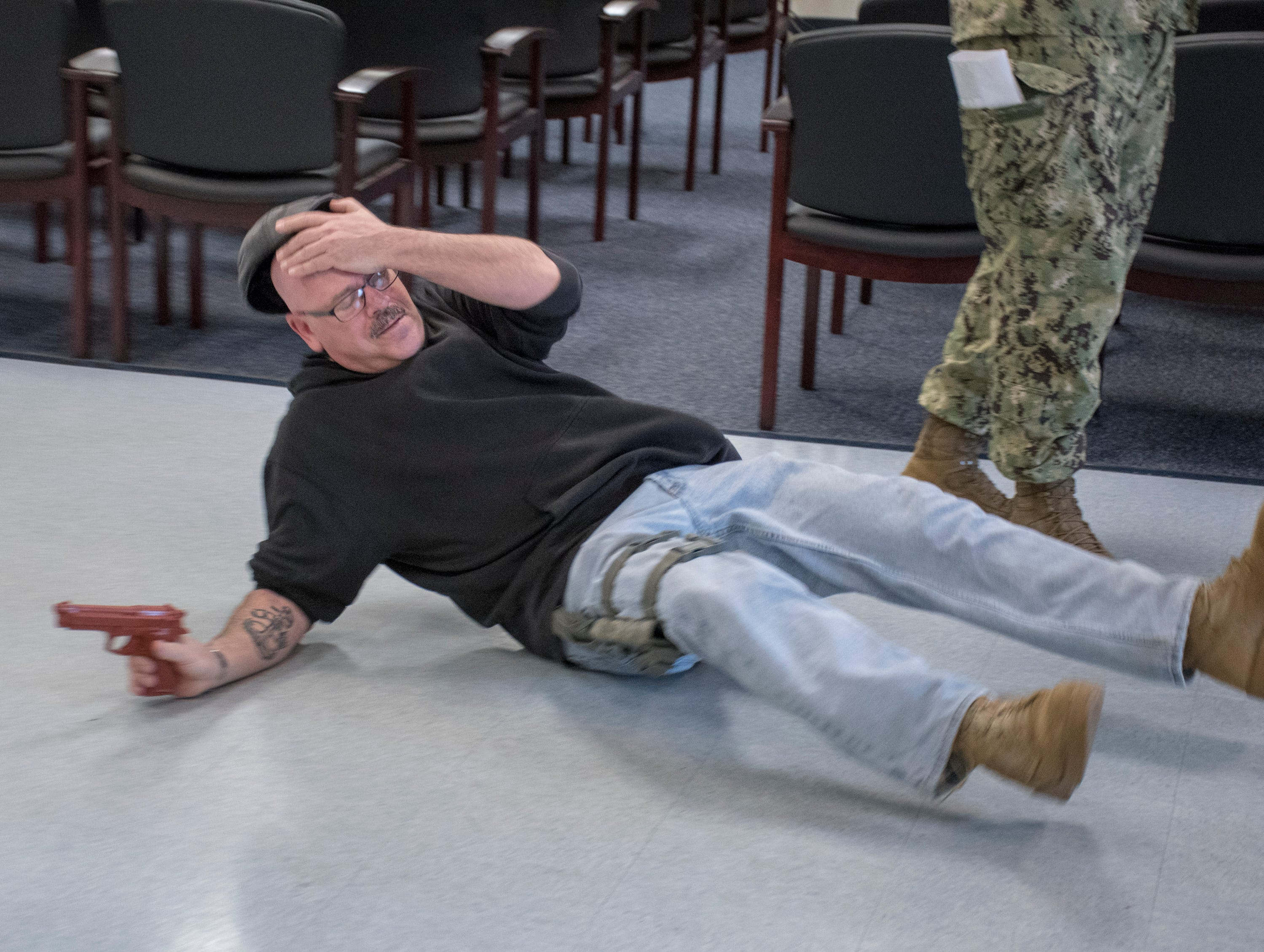 Portraying an armed intruder,  Senior Chief Aviation Structural Mechanic Pasquale Moreland falls to the ground after being shot in the Personnel Support Detachment building during Exercise Solid Curtain-Citadel Shield, an annual security exercise is conducted at NAS Pensacola on Tuesday, February 4, 2019.