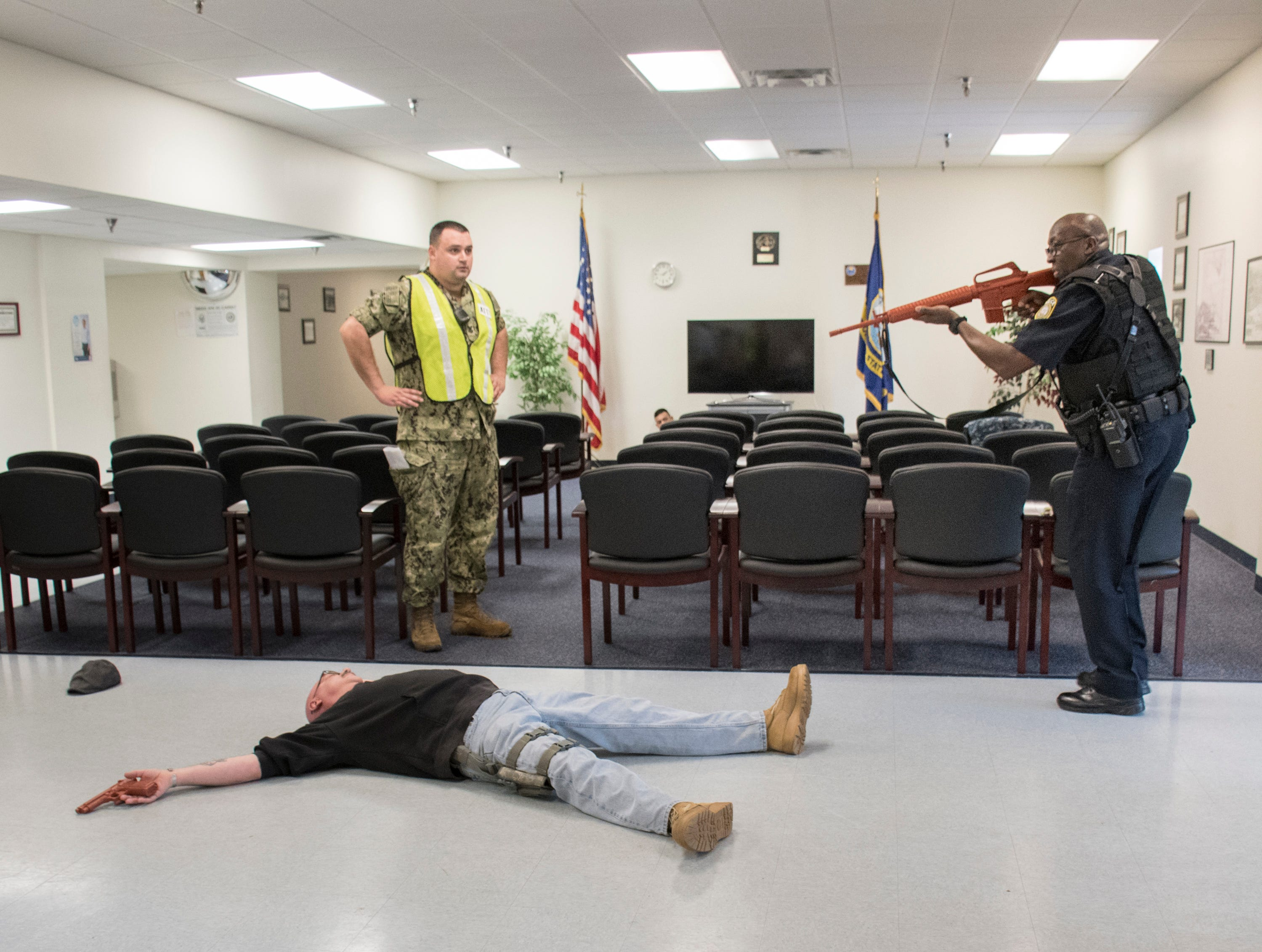 Portraying an armed intruder,  Senior Chief Aviation Structural Mechanic Pasquale Moreland lays on the ground after being shot as NAS Pensacola Police Officer Samuel Watkins enters the Personnel Support Detachment building during Exercise Solid Curtain-Citadel Shield, an annual security exercise is conducted at NAS Pensacola on Tuesday, February 4, 2019.