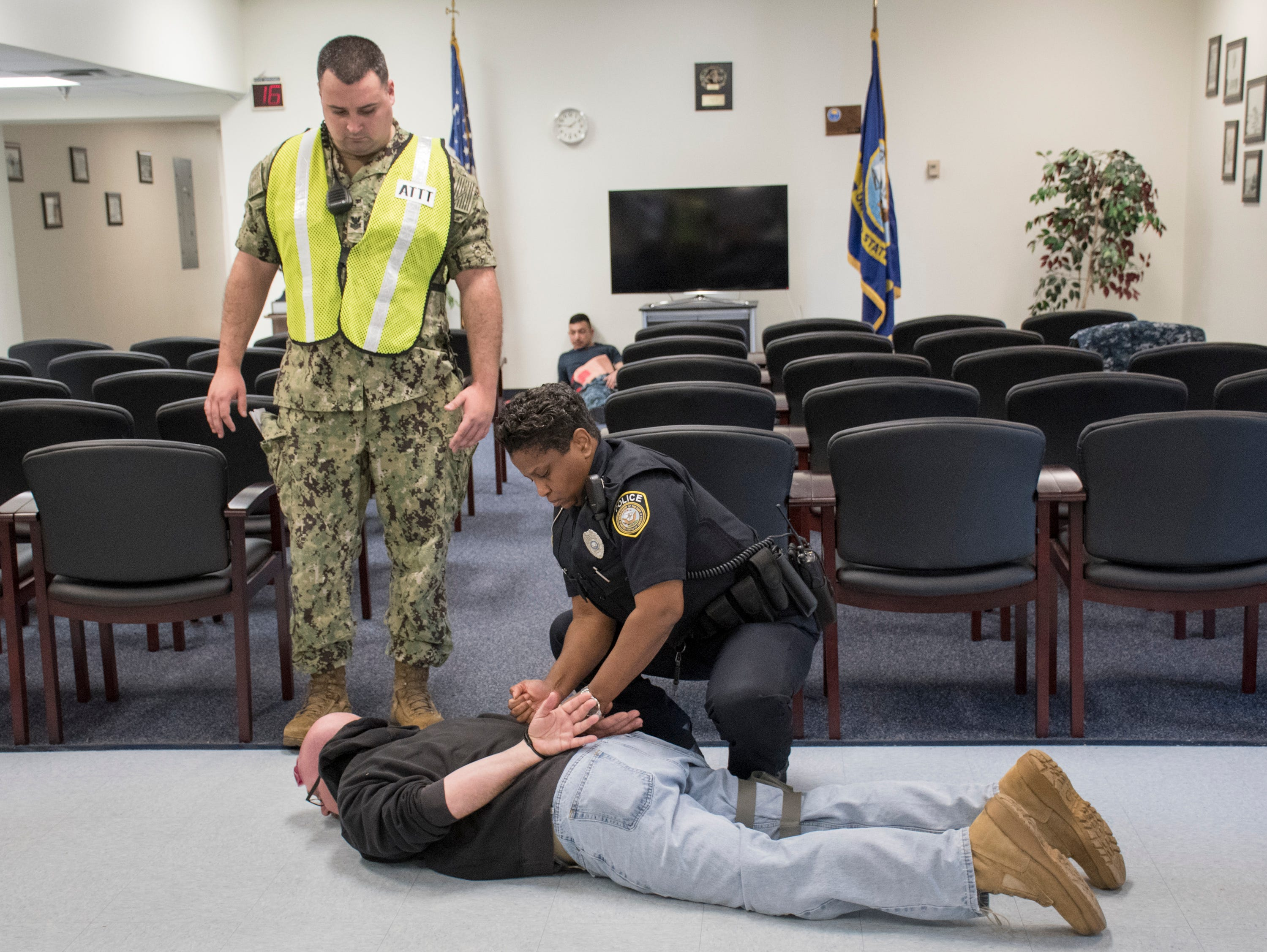 NAS Pensacola Police Officer Sophia Barnes handcuffs Senior Chief Aviation Structural Mechanic Pasquale Moreland, who is portraying an armed intruder, in the Personnel Support Detachment building during Exercise Solid Curtain-Citadel Shield, an annual security exercise is conducted at NAS Pensacola on Tuesday, February 4, 2019.