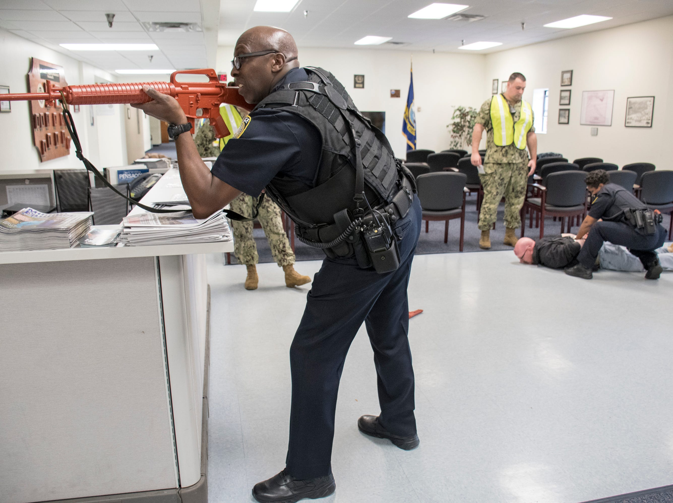 NAS Pensacola Police Officer Samuel Watkins, left, secures the room as his partner Sophia Barnes handcuffs Senior Chief Aviation Structural Mechanic Pasquale Moreland, who is portraying an armed intruder, in the Personnel Support Detachment building during Exercise Solid Curtain-Citadel Shield, an annual security exercise is conducted at NAS Pensacola on Tuesday, February 4, 2019.